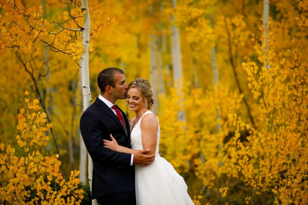 A groom kisses his bride in a grove of aspen trees during their fall colors wedding at Camp Hale