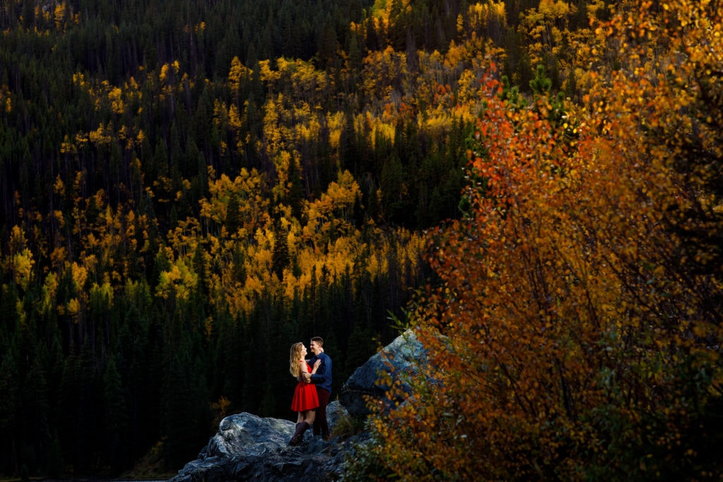 A couple pose on a rock surrounded by golden fall colors at Officers Gulch during their fall mountain engagement photos near Frisco Colorado
