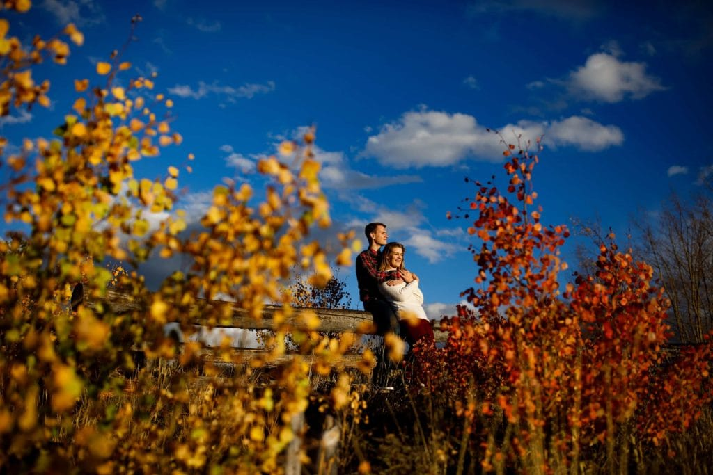 Holly and Hayden are surrpunded by fall color and blue skies during their fall mountain engagement photos