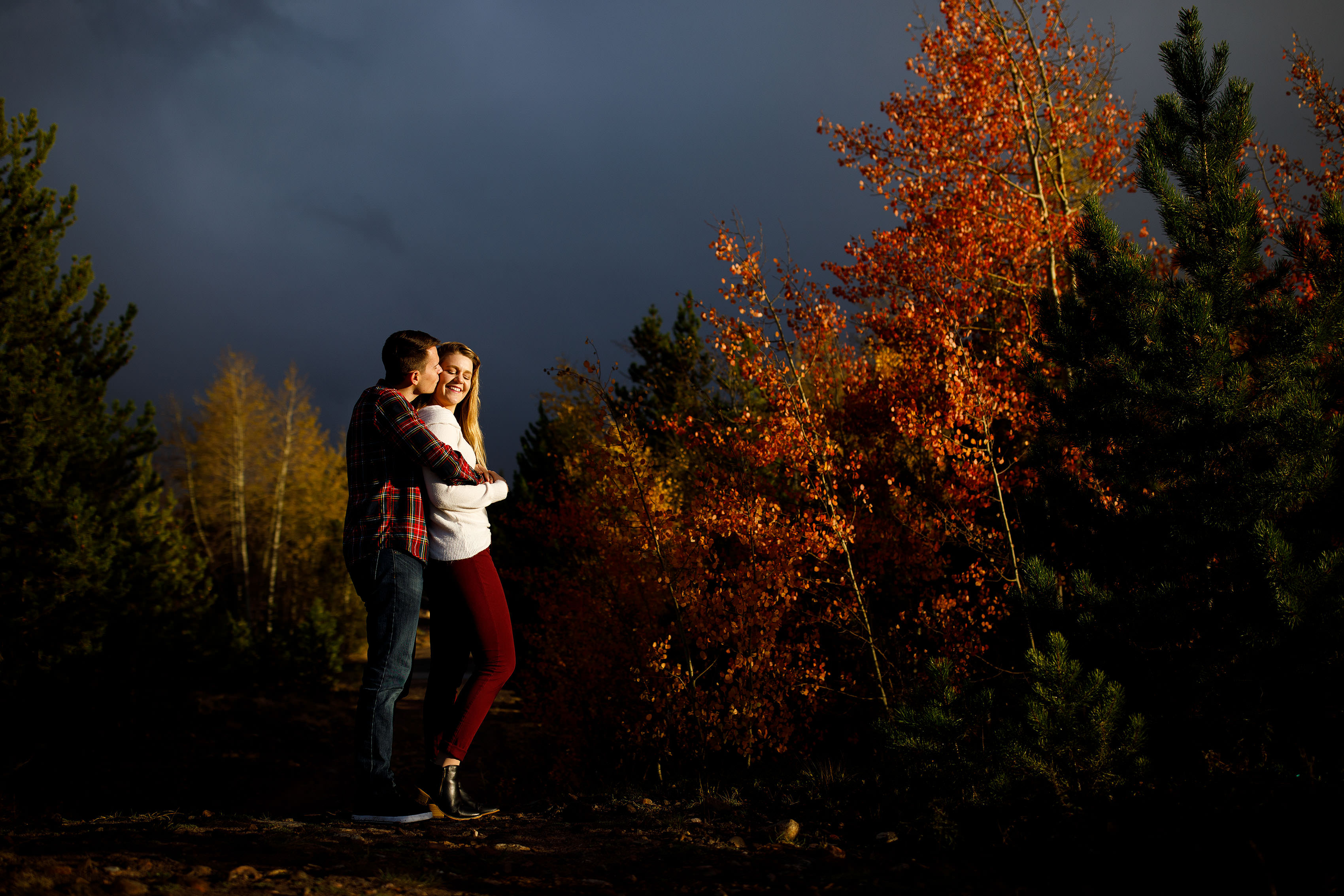 The couple share a moment during their fall mountain engagmenet near a grove of colorful aspen trees in Frisco Colorado