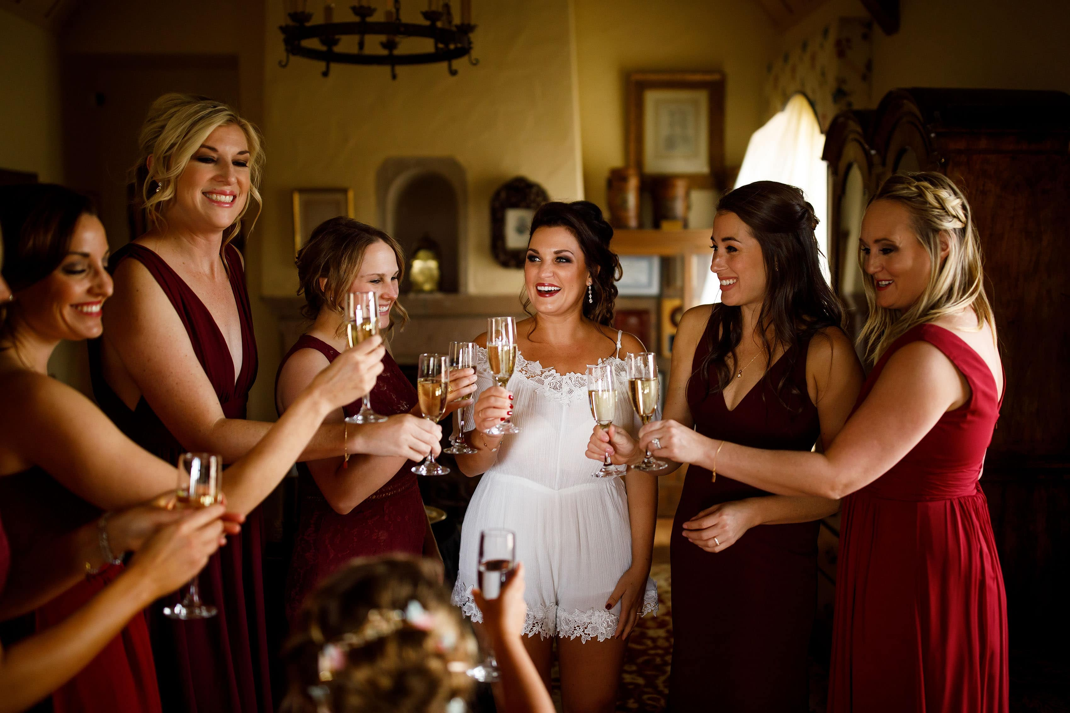The bride shares a champagne toast with her bridesmaids while getting ready for her Cherokee Ranch & Castle wedding