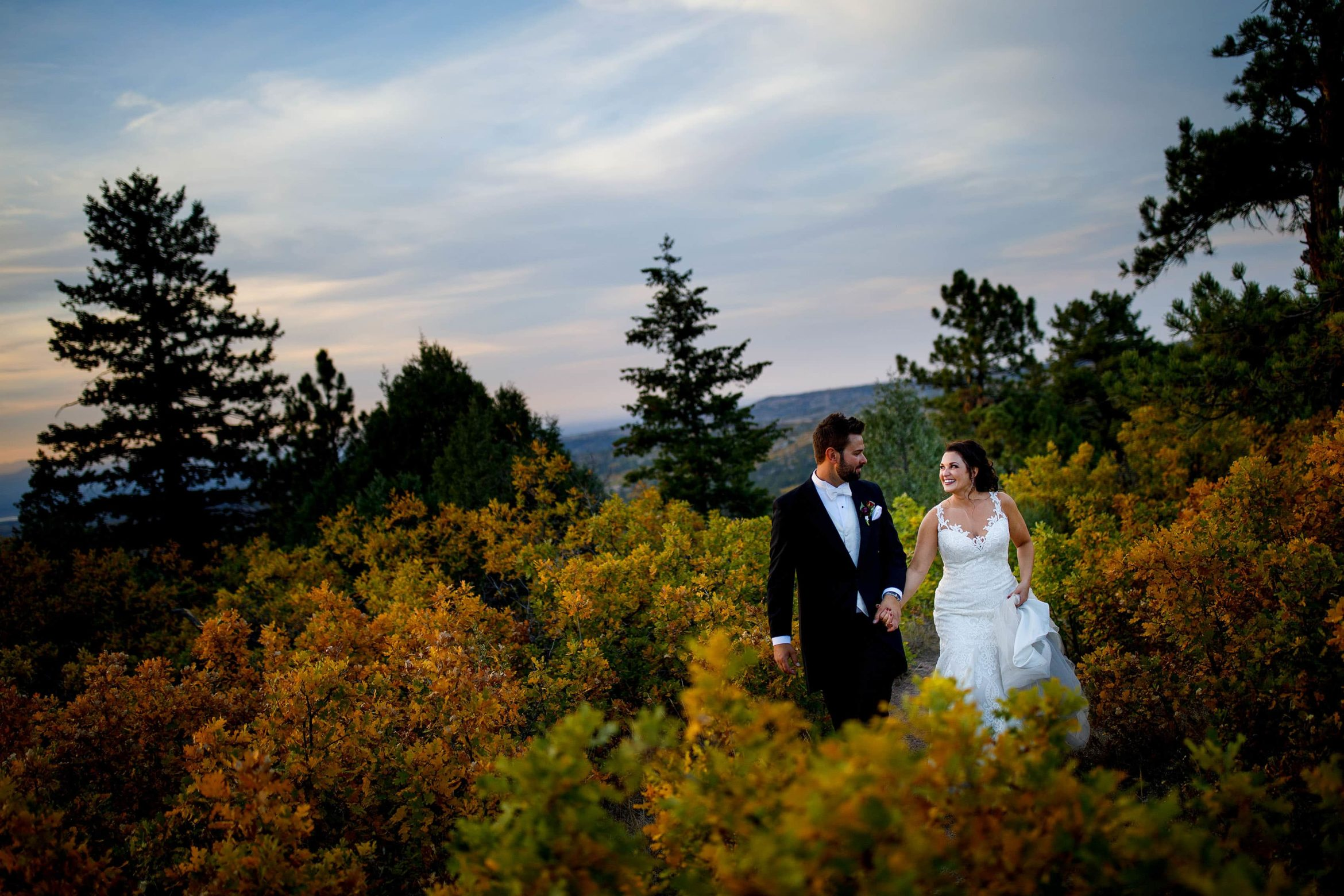 Melissa and Jordan walk together near Cherokee Ranch and Castle after their wedding in Sedalia