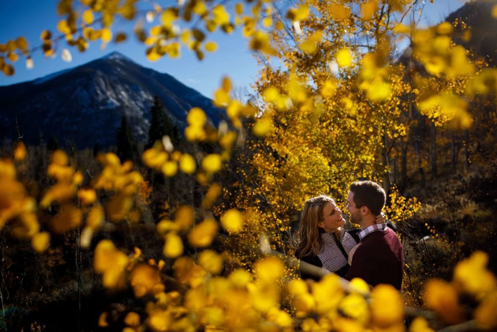 Julia and Micah embrace near golden aspen trees during their fall Frisco engagement photos in Colorado