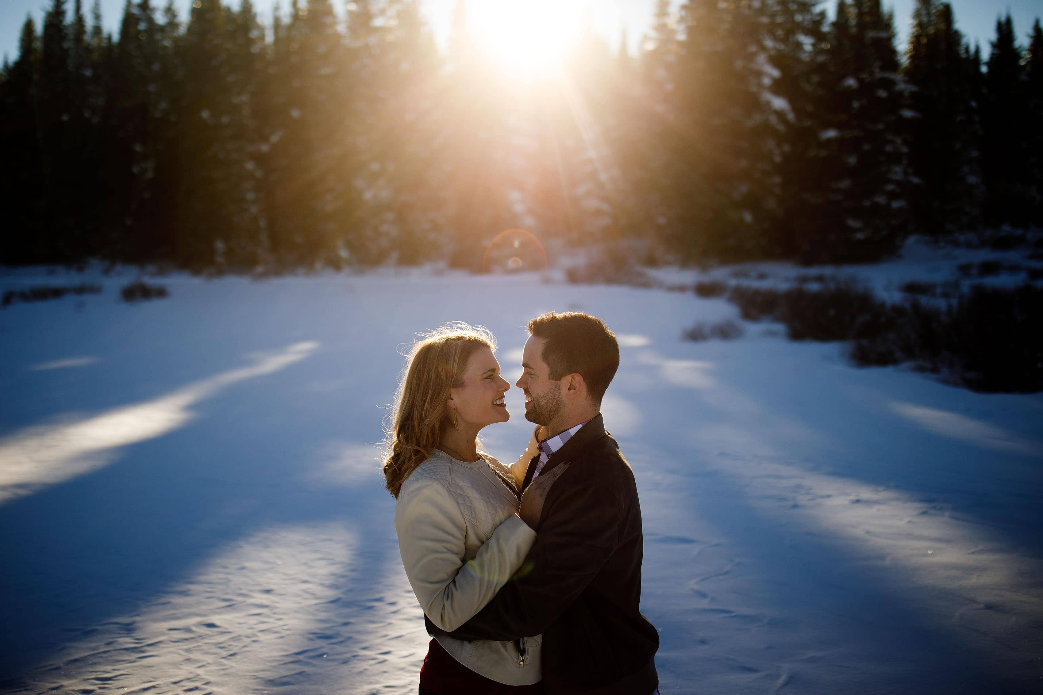 Micah and Julia pose together in the snow as the sun sets behind them on Shrine Pass near Vail
