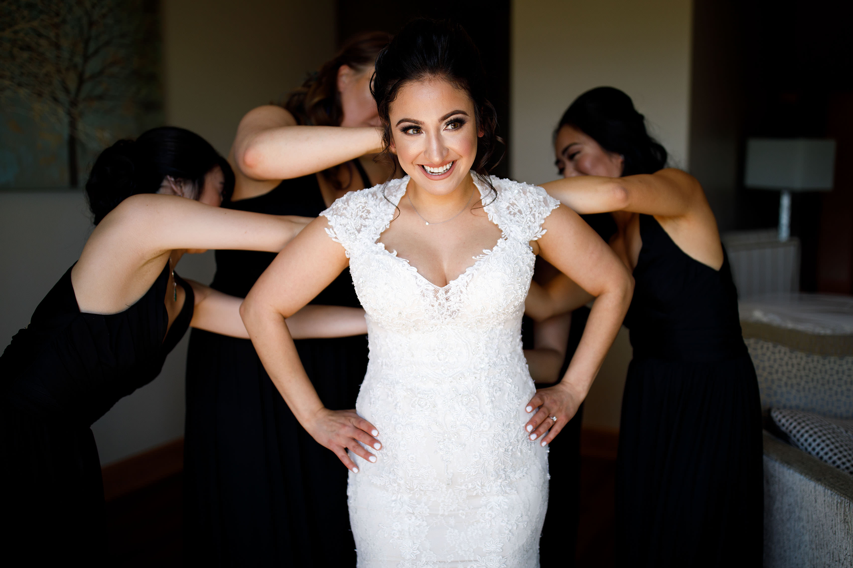 A bride gets help getting into her wedding dress by bridesmaids