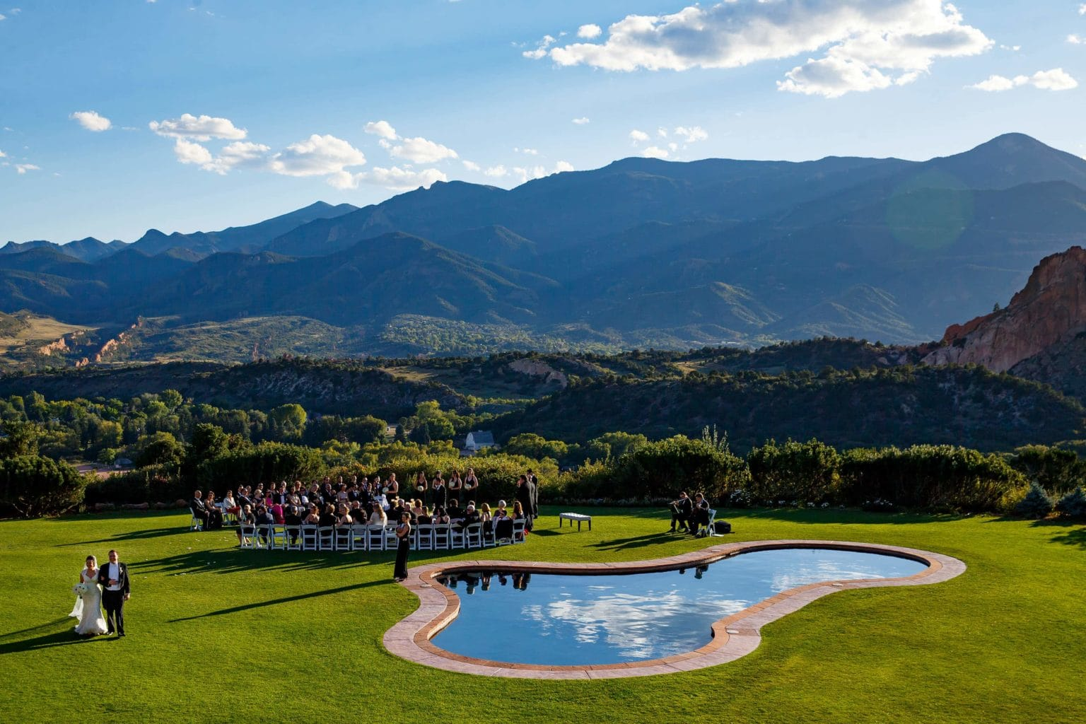 Shabnam and Joseph walk out of their Garden of the Gods Resort wedding ceremony by the pool