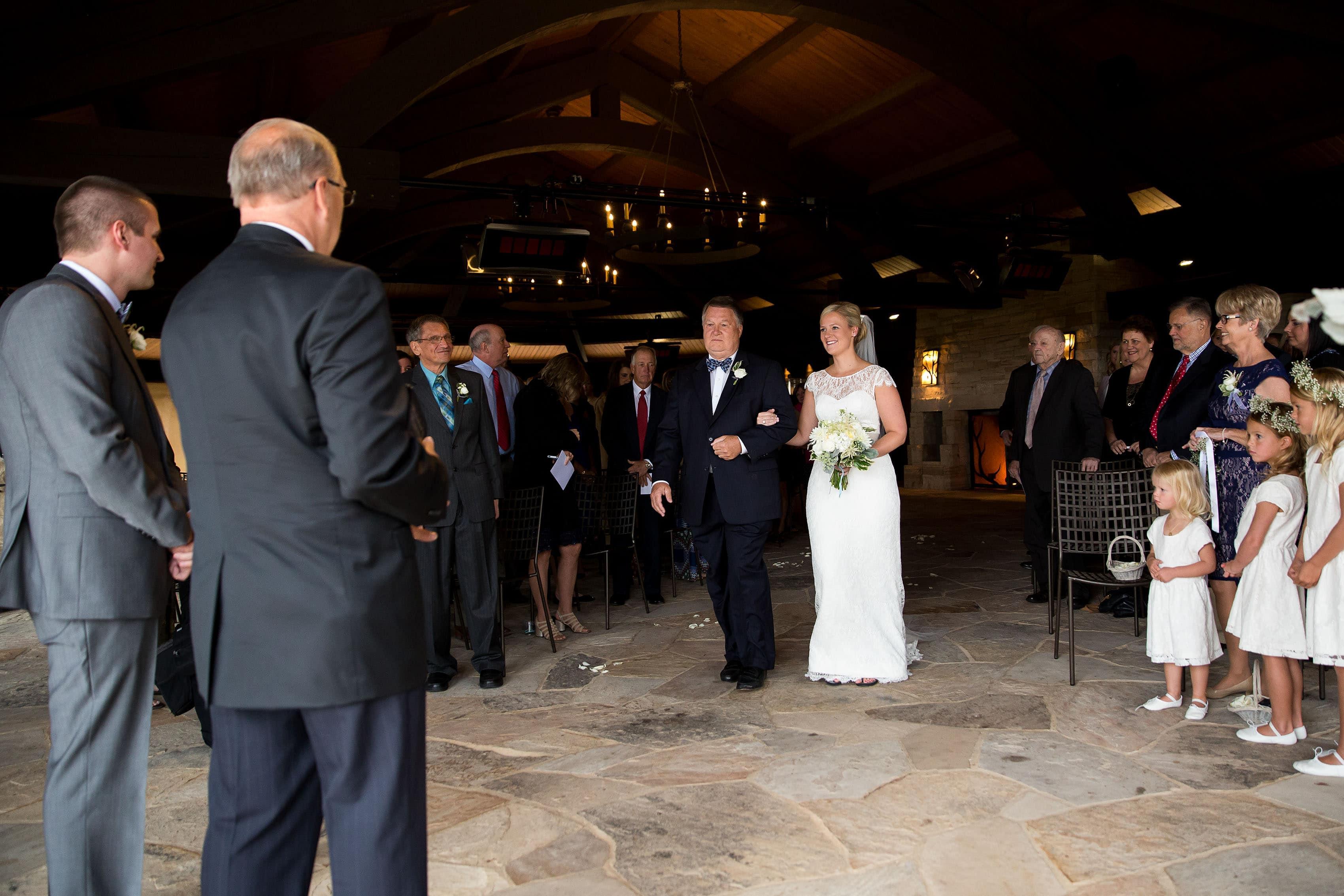 Bride walks down the aisle during a Sanctuary Golf Course wedding