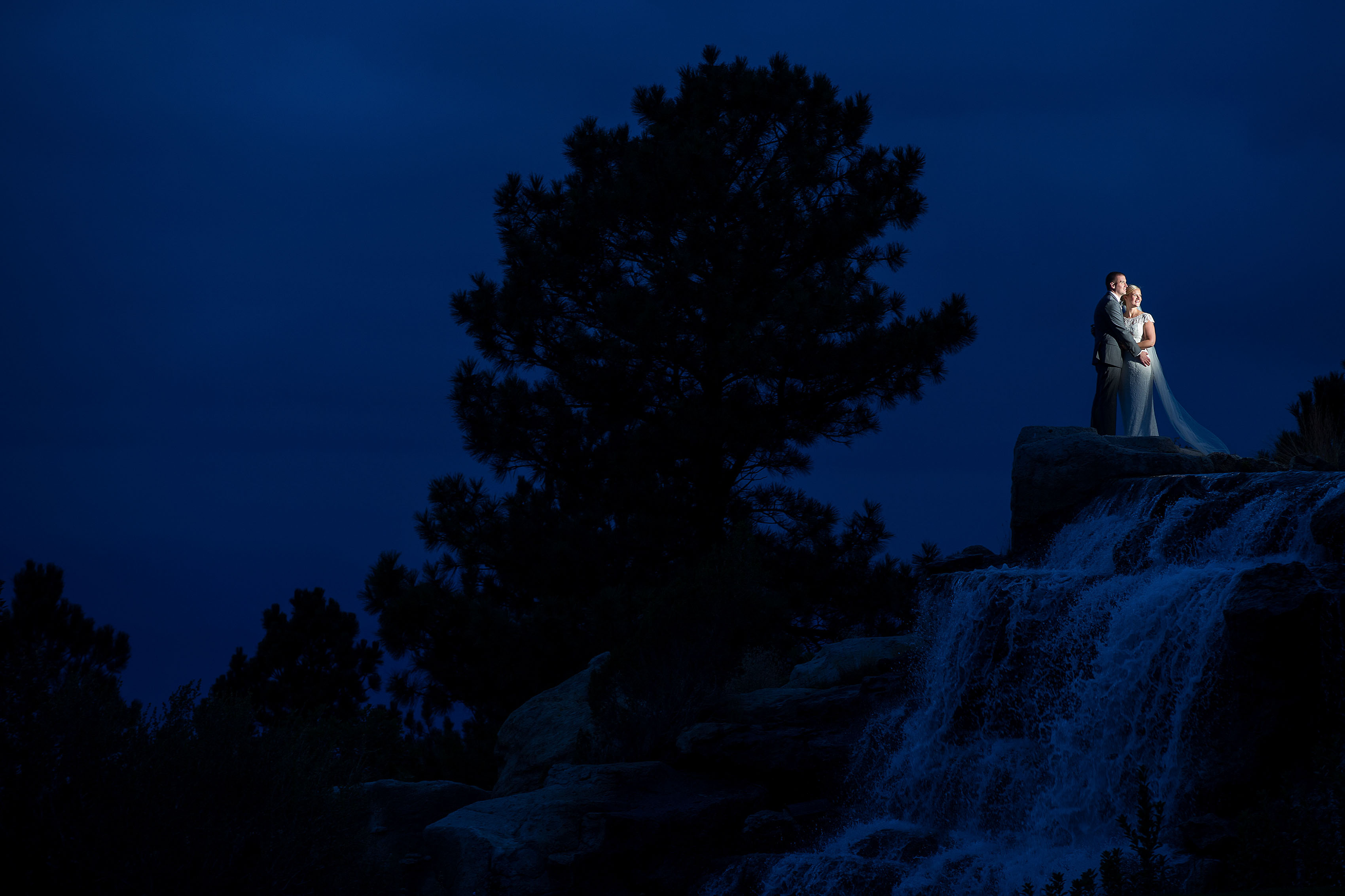 Couple poses near the waterfall at twilight during their Sanctuary Golf Course wedding
