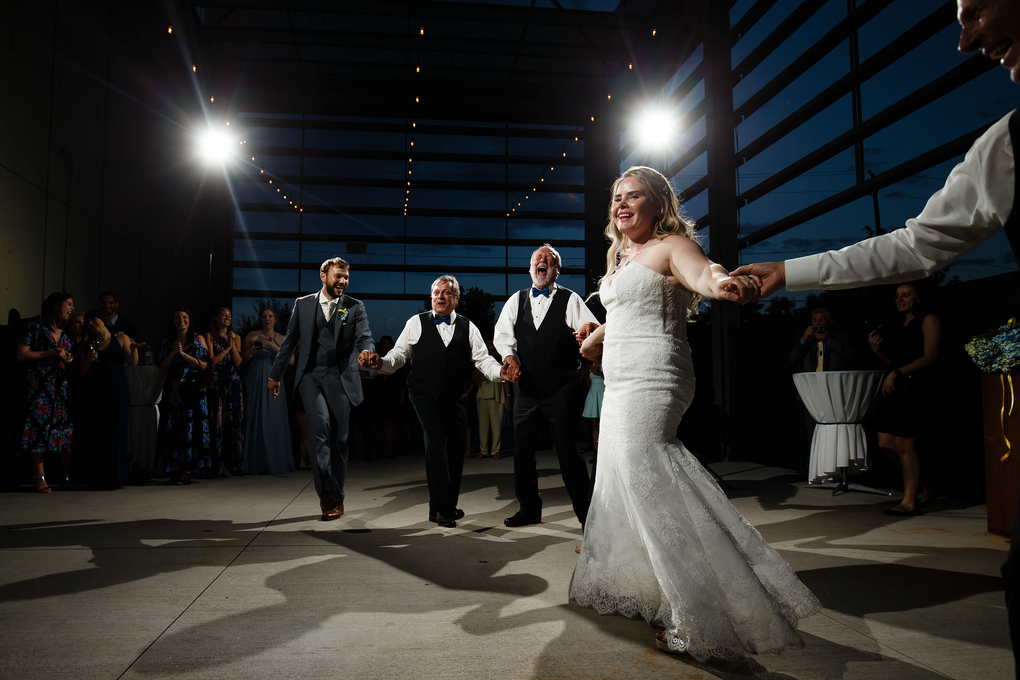 The bride and groom dance with their family during twilight at Space Gallery
