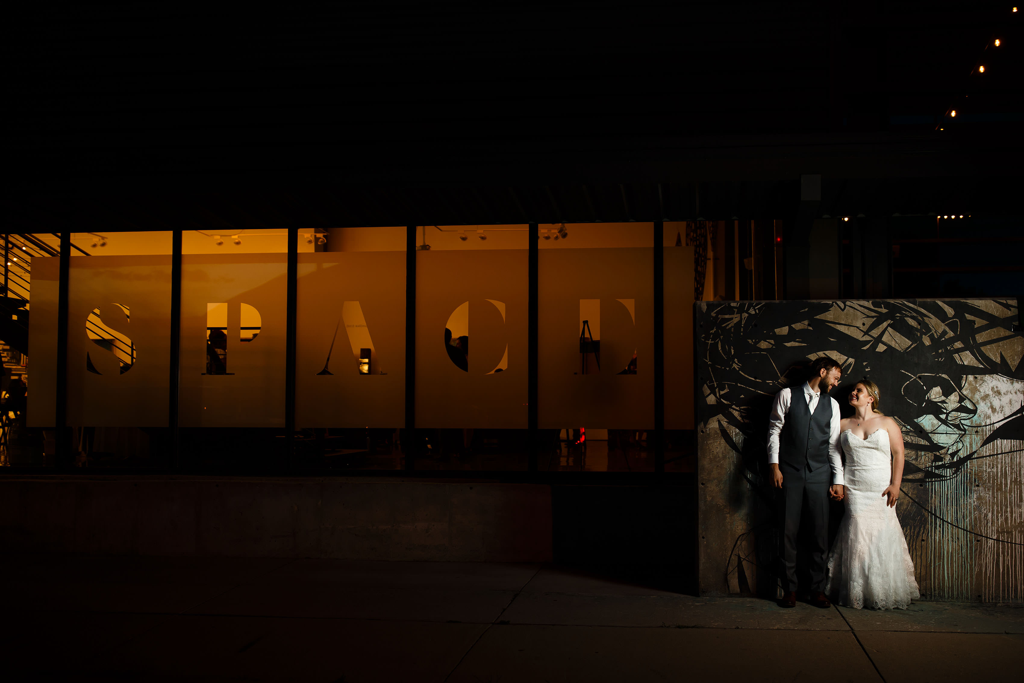 The couple pose outside Space Gallery on their wedding day