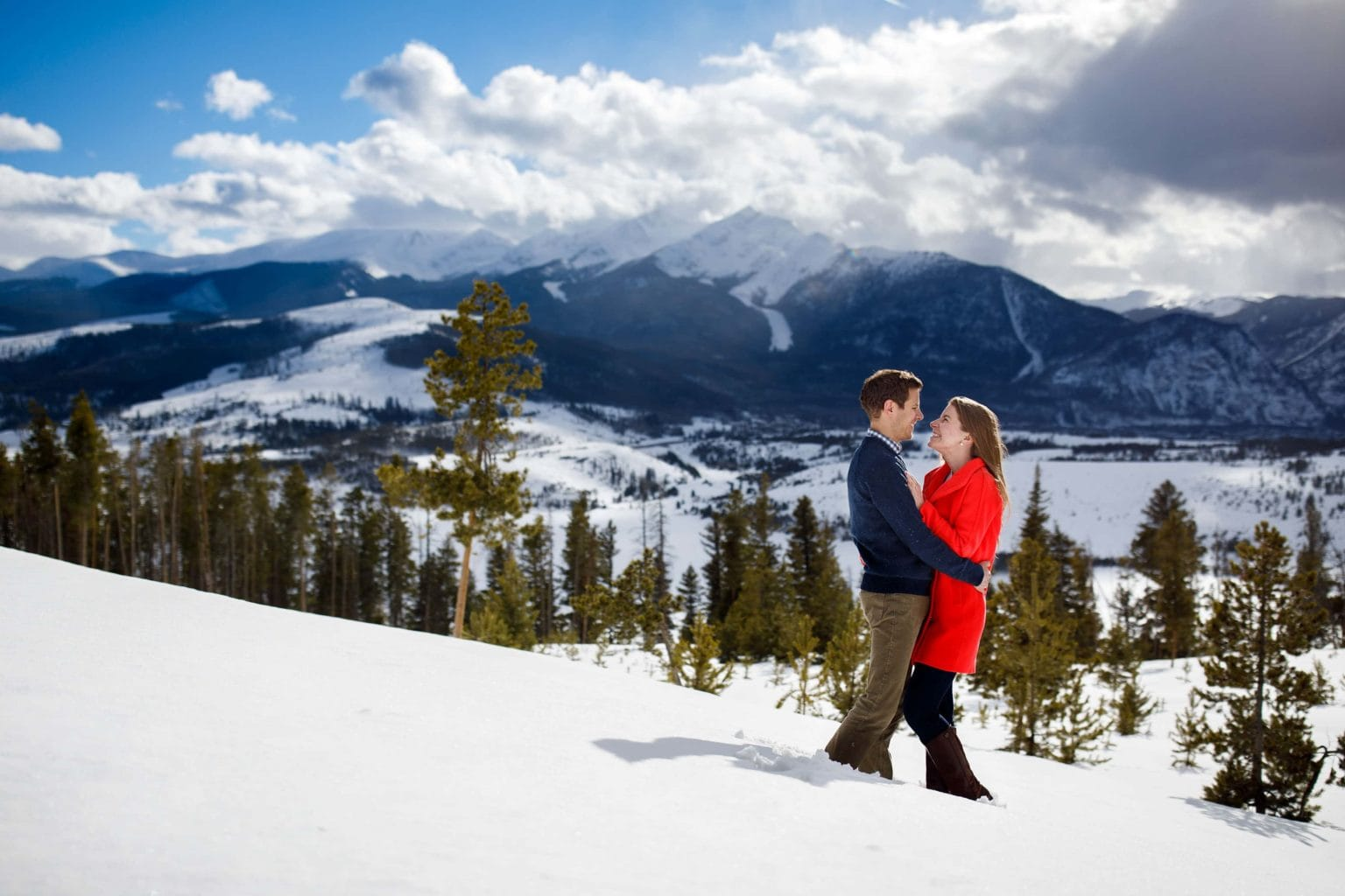 Jessica wears a red coat while embracing with Mike in the snow at Sapphire Point during their winter keystone engagement