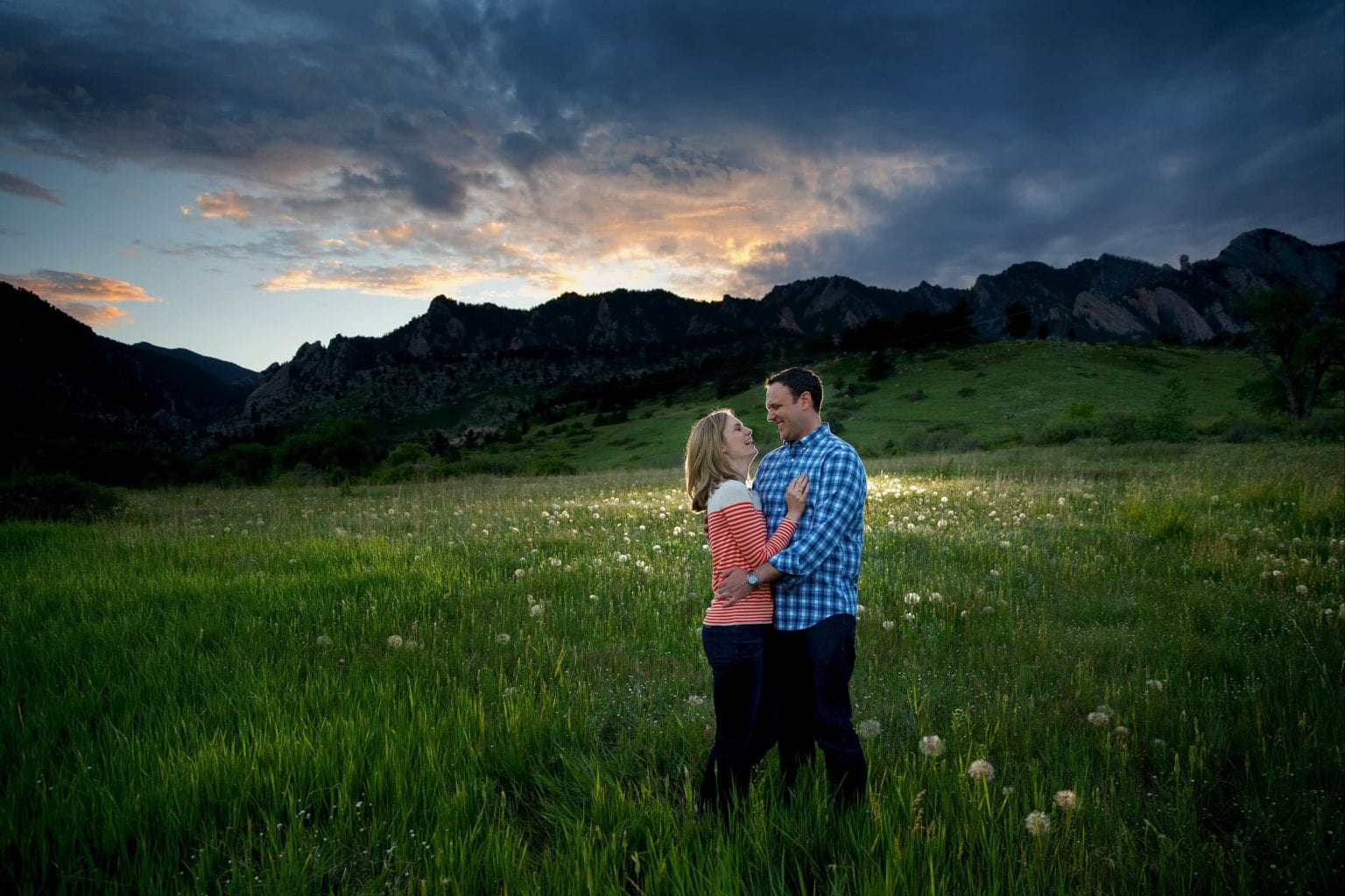 A couple embrace in a meadow at sunset in Eldorado Springs during their engagement session