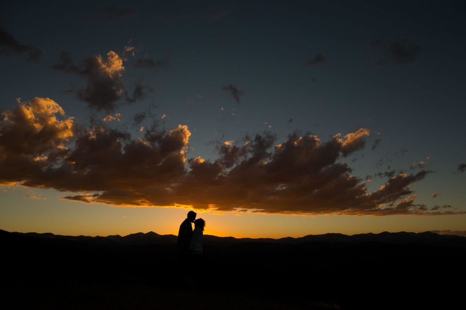 A couple kisses at sunset during their Mount Evans engagement