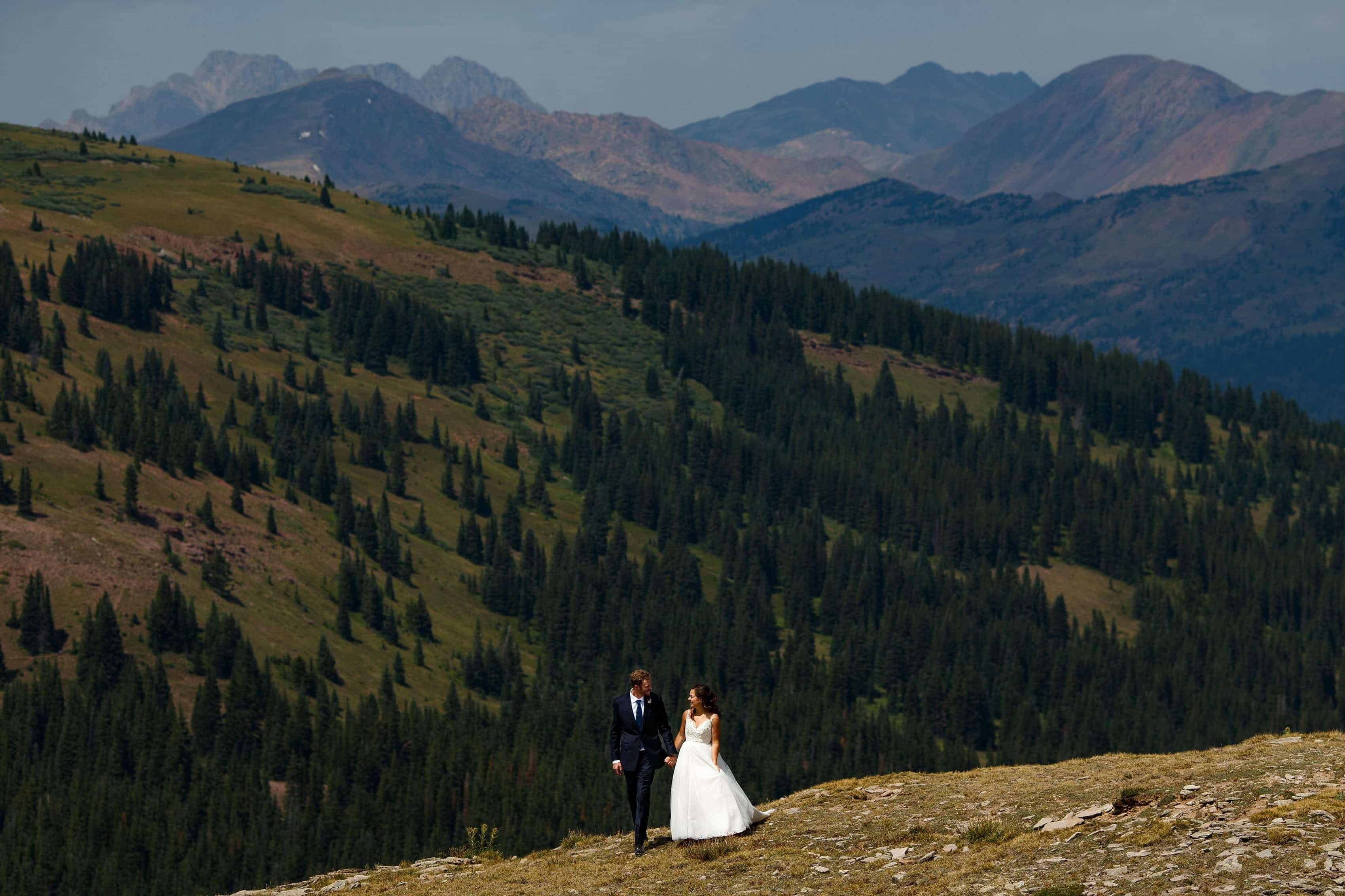 Newlyweds walk on the top of Ptarmigan Pass during their Camp Hale wedding