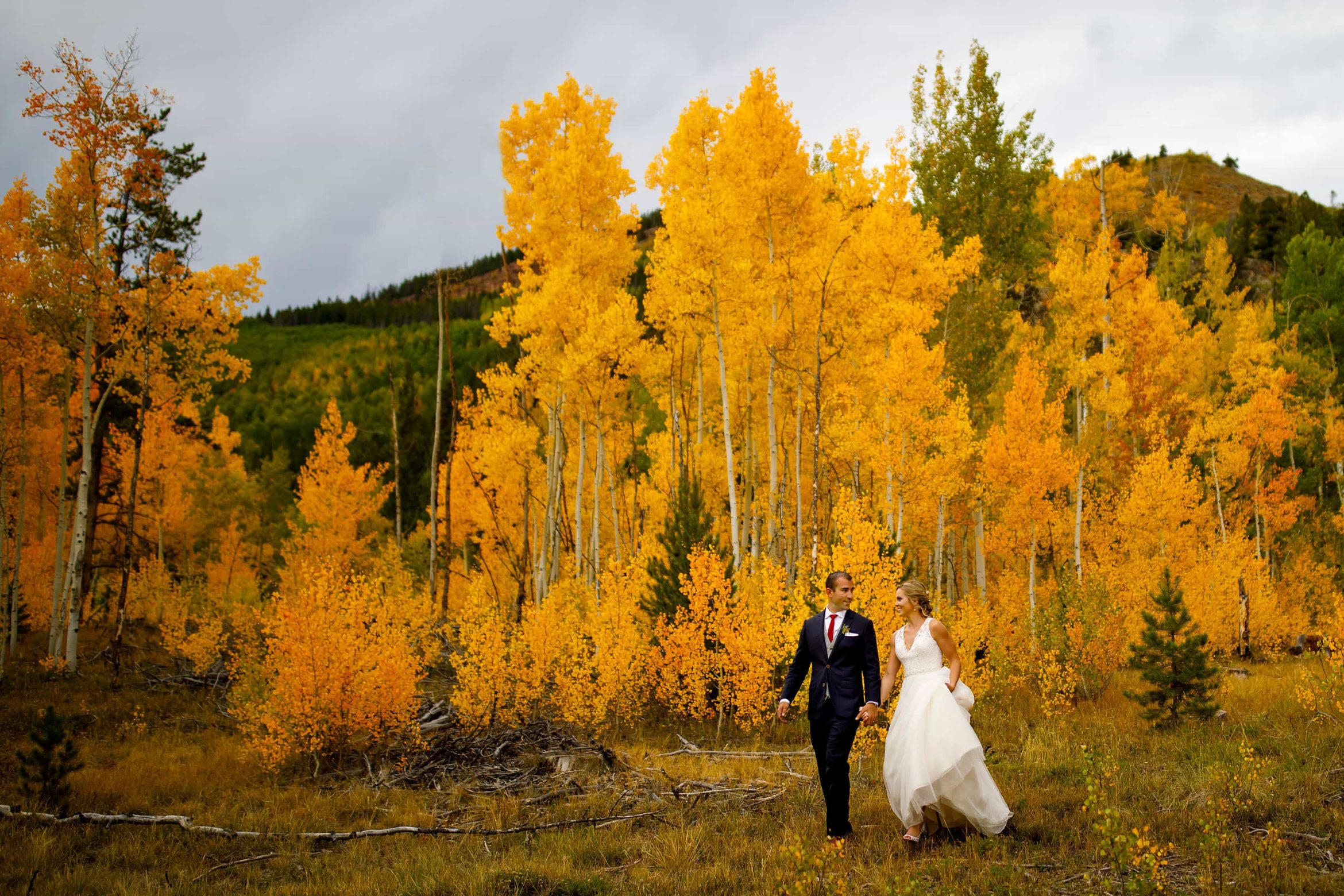 Newlyweds walk together near a grove of aspen trees during their fall colors wedding at Camp Hale