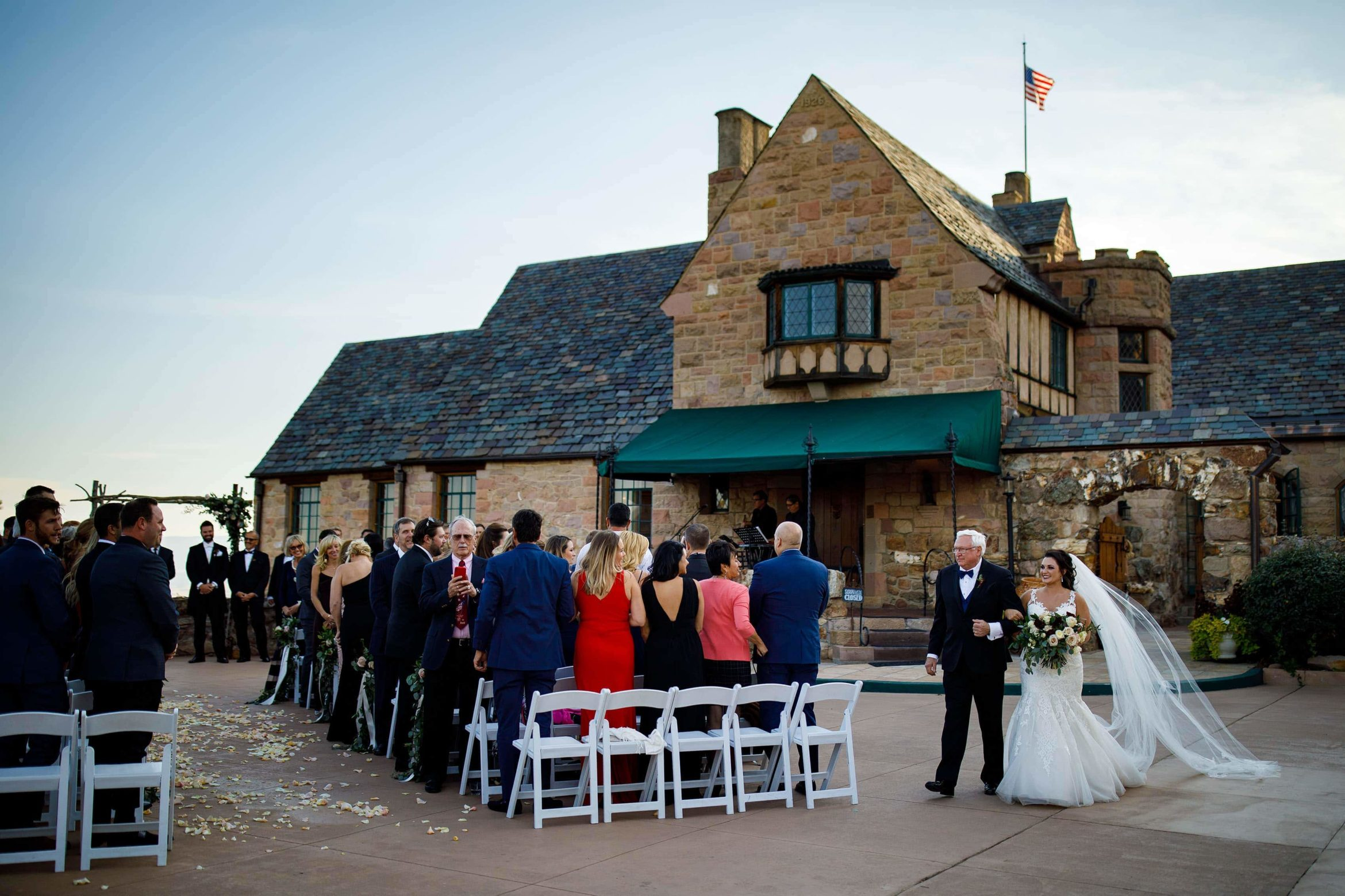 A bride walks down the aisle with her father at Cherokee Ranch and Castle Foundation