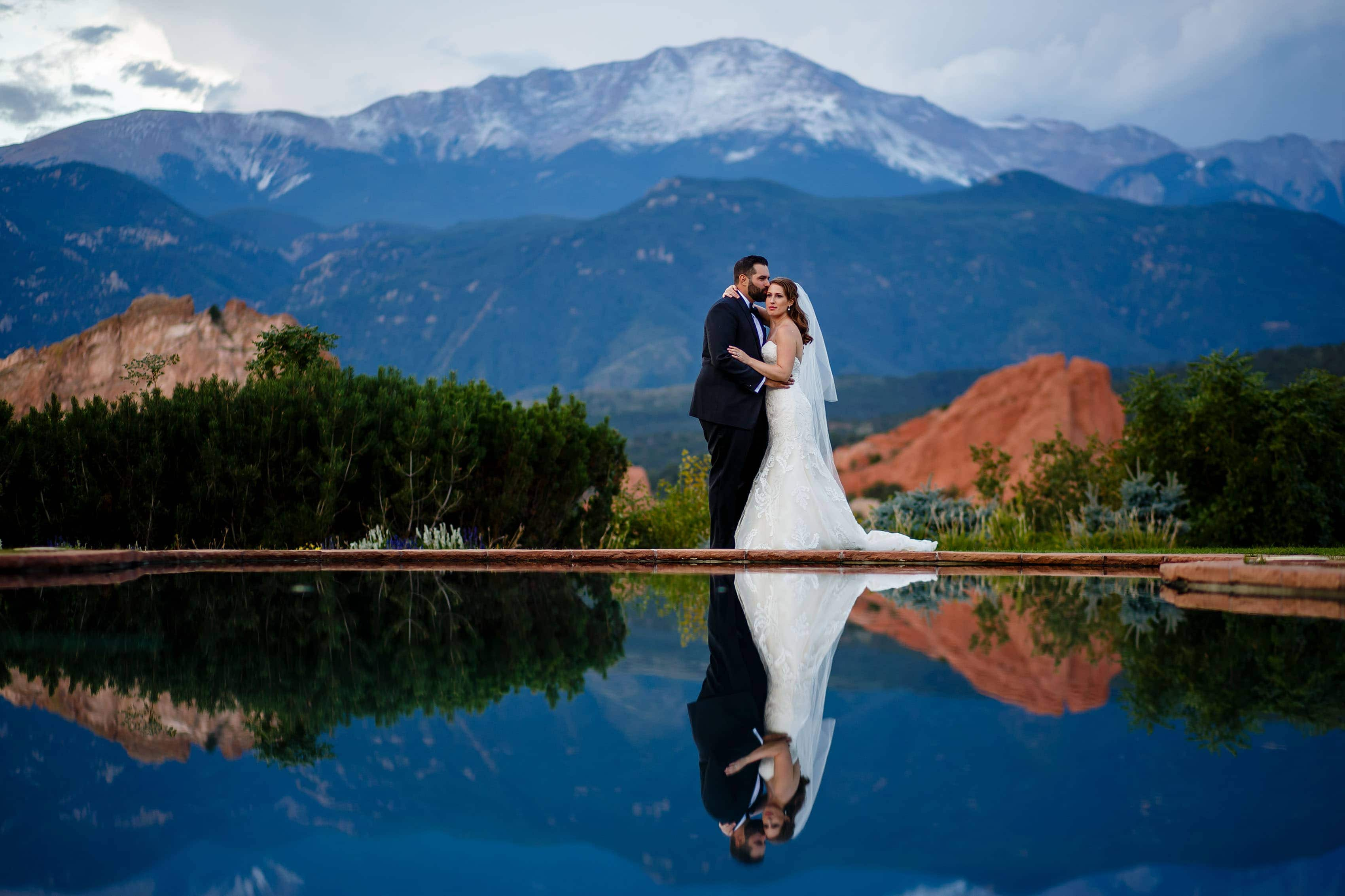 Reflected by the pool, Devan and Joshua share a moment together as Pikes Peak provides the backdrop after their wedding at Garden of the Gods Club