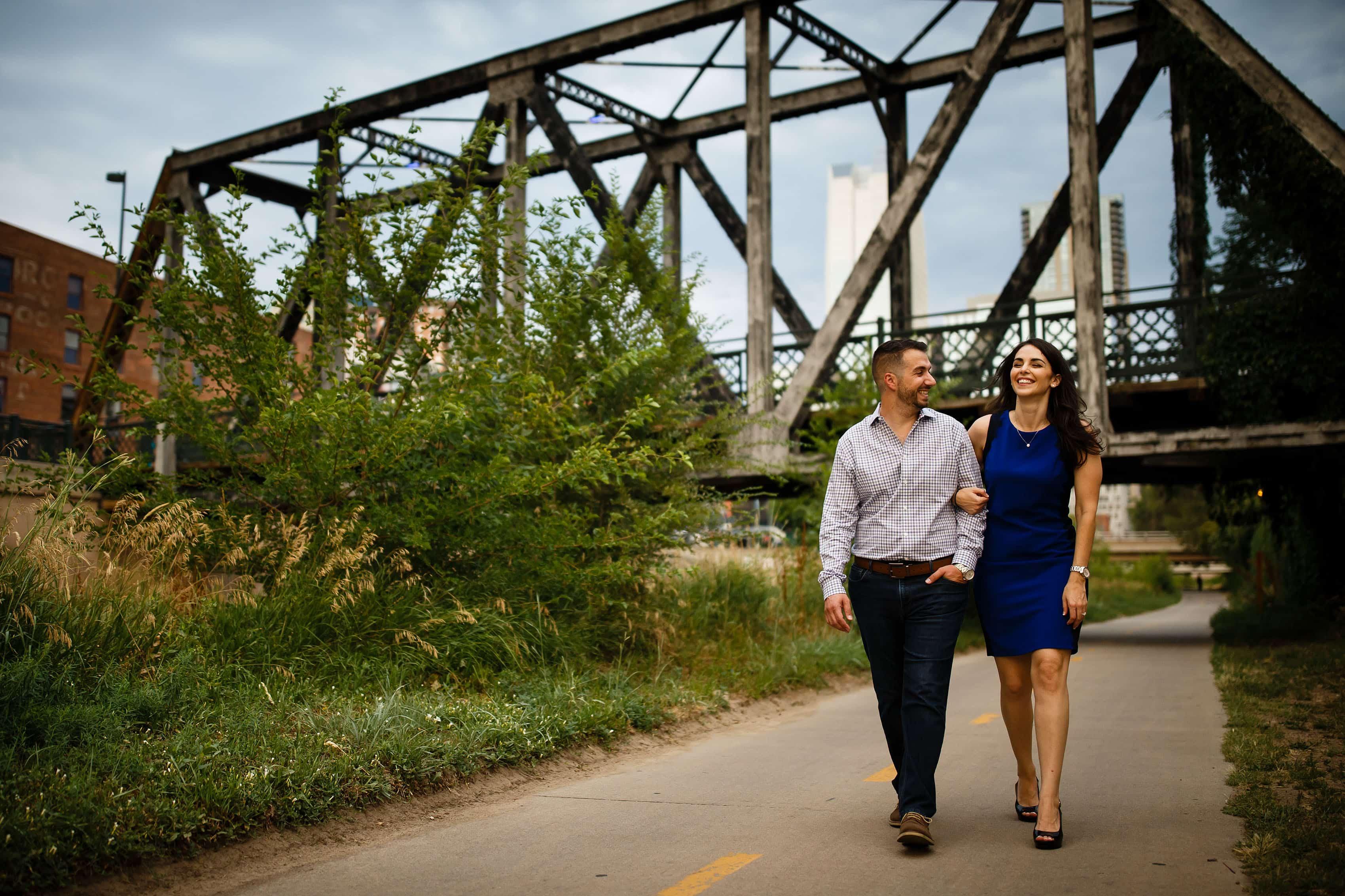 Couple walk and laugh on the Cherry Creek path near the Wynkoop Street Bridge in Denver