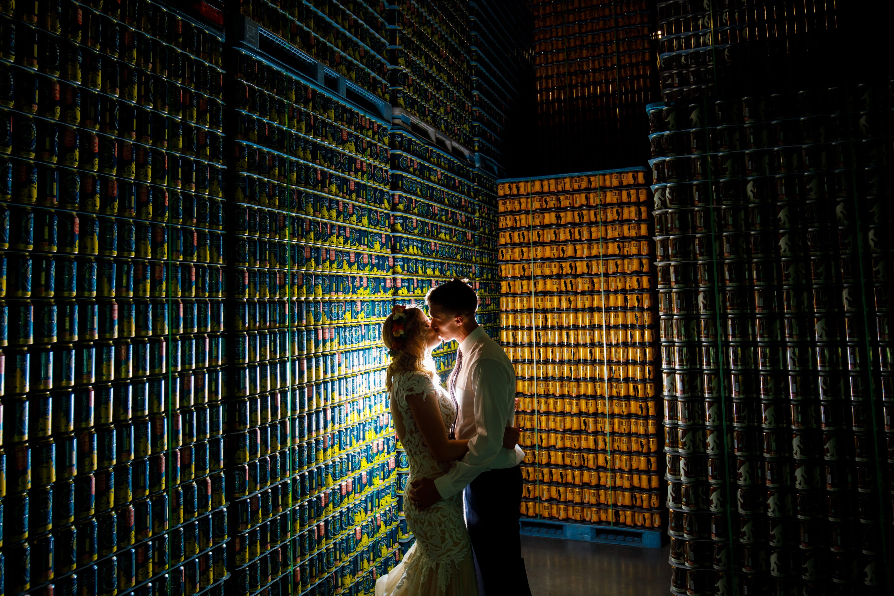 A couple kisses near a stack of beer cans during a Great Divide Brewery wedding