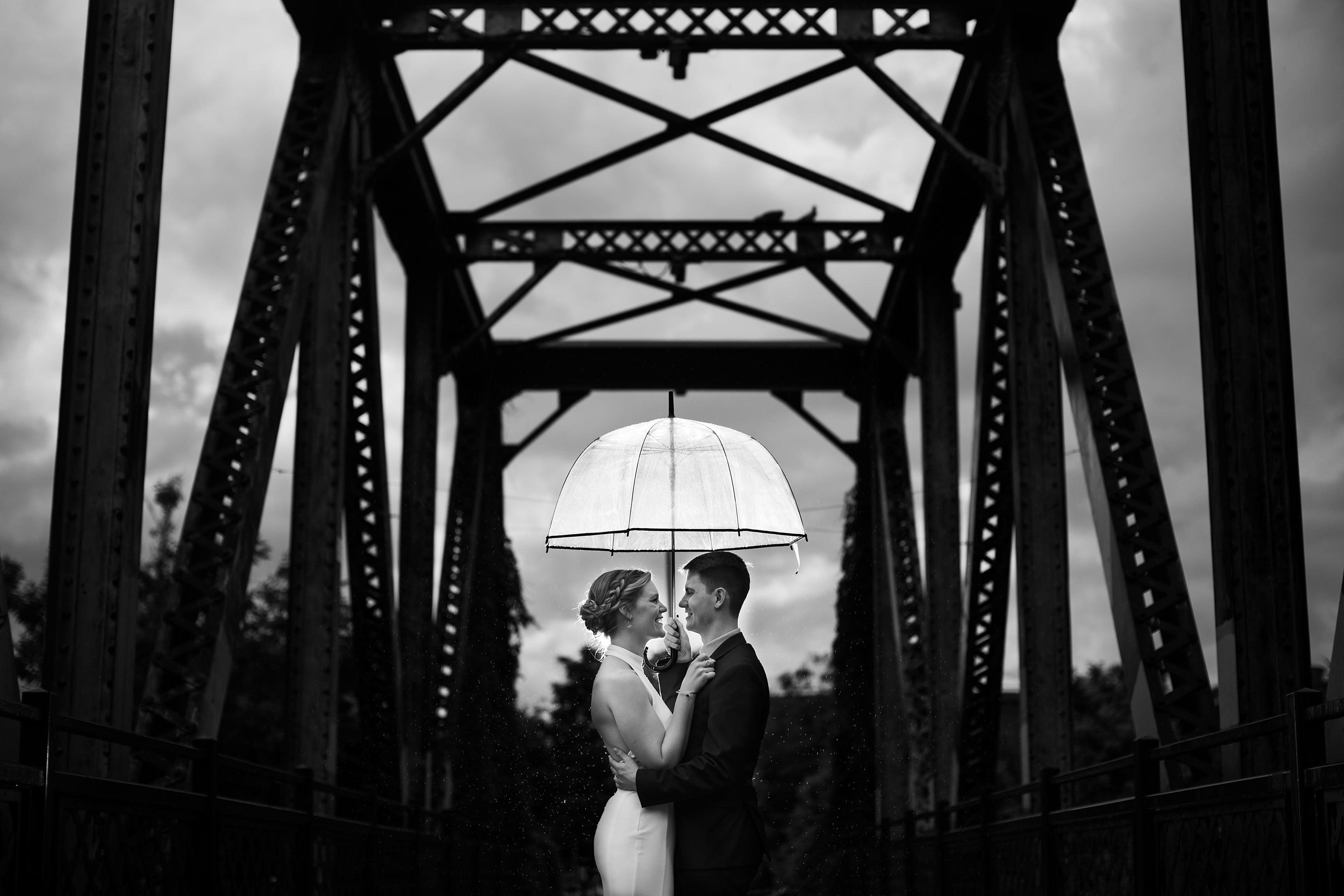 Wynkoop Street Bridge wedding portrait in the rain with an umbrella