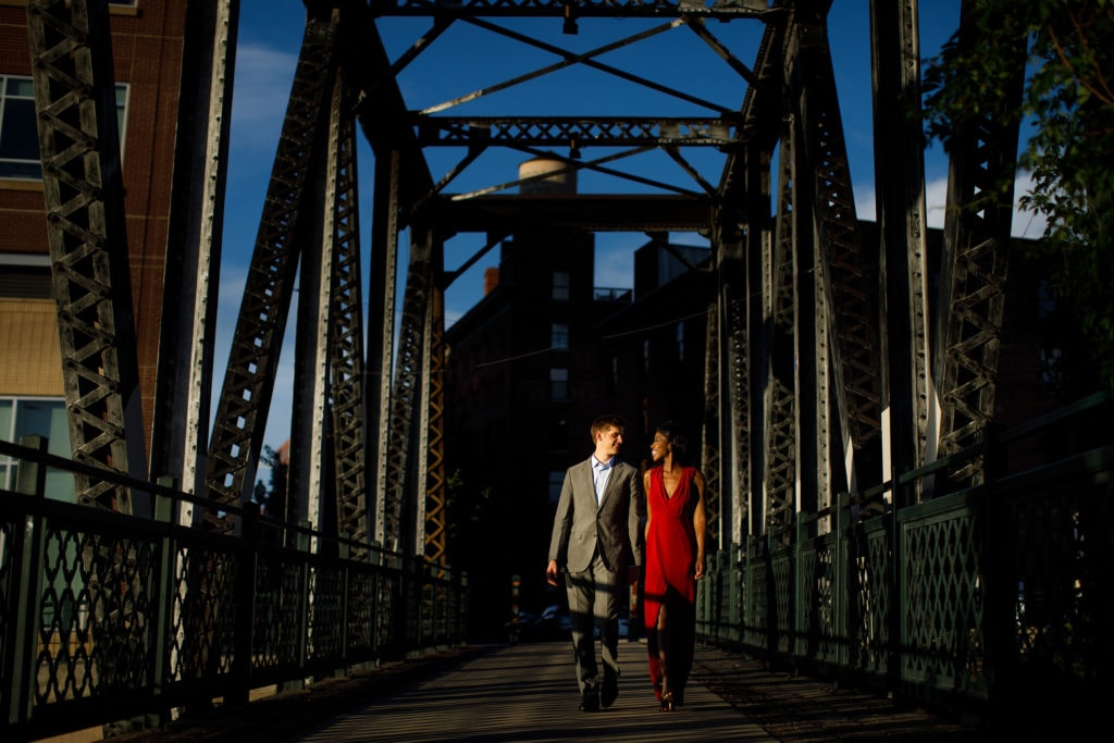 Man in a suit and woman in a red dress walk together at sunset on the Wynkoop Street Bridge