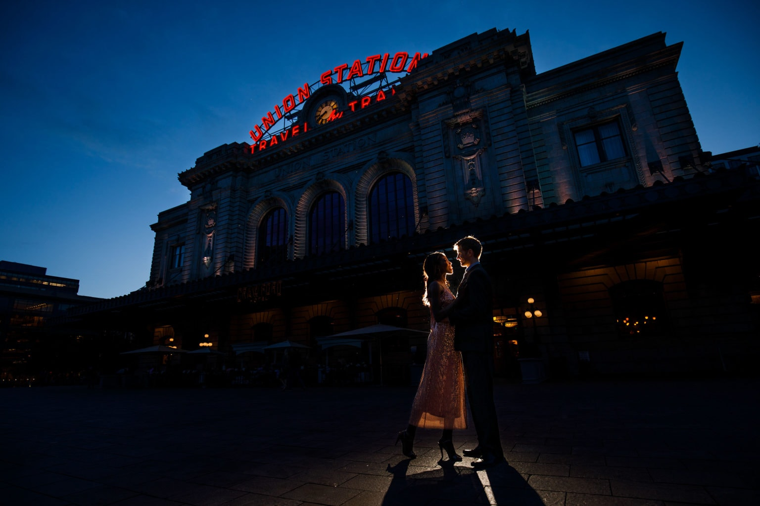 Ewo and Henry pose together at twilight in front of Denver Union Station during their engagement photos