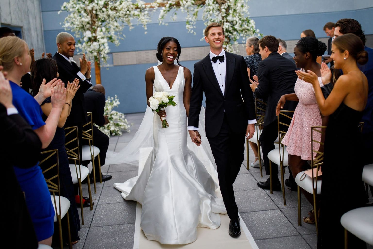the bride and groom walk down the aisle following their wedding at the denver museum of nature and science