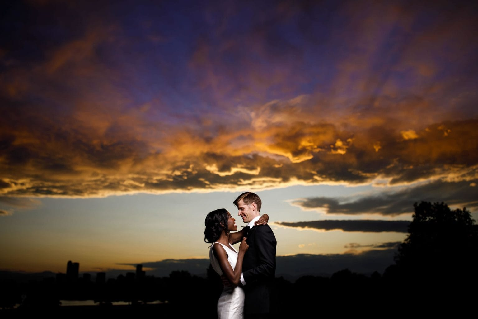 A couple pose together under a Denver sunset during their wedding day