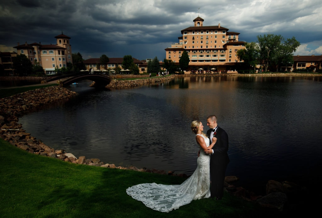 The bride and groom pose near Cheyenne Lake at The Broadmoor during their August wedding