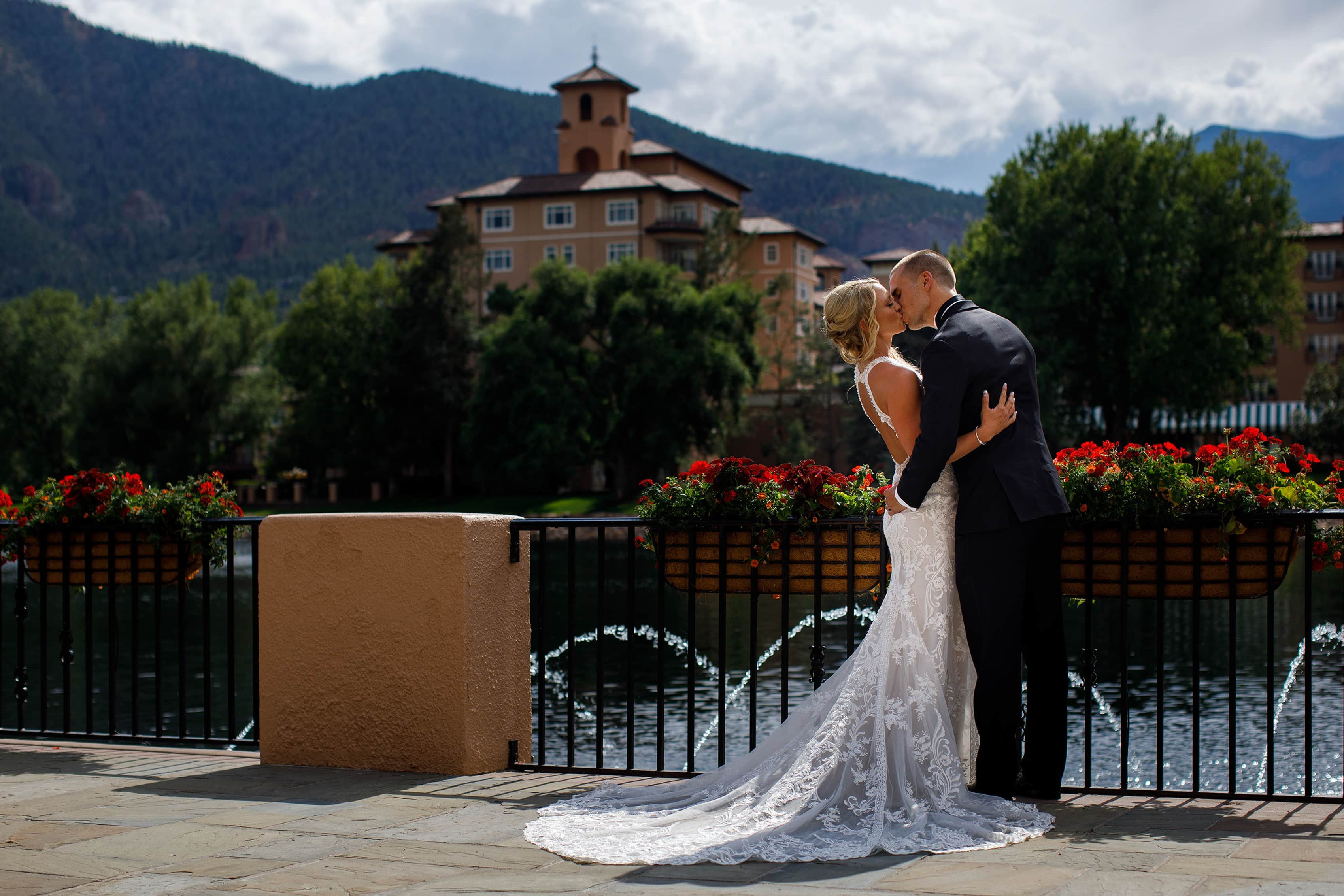 Bride and groom kiss on the lake terrace at The Broadmoor in Colorado Springs