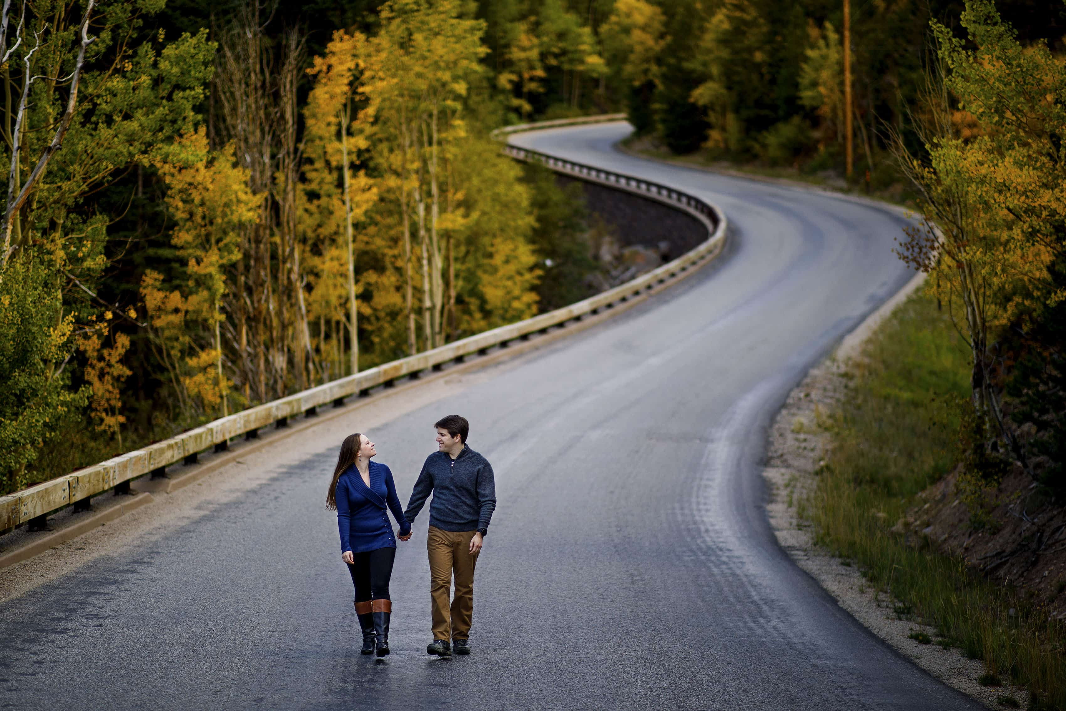 A couple walk together on Guanella Pass road lined with changing aspen trees during their fall engagement session