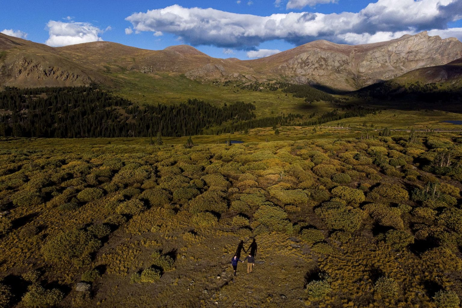 An arial drone photo of a couple walking together at Guanella Pass during their fall engagement session in Colorado