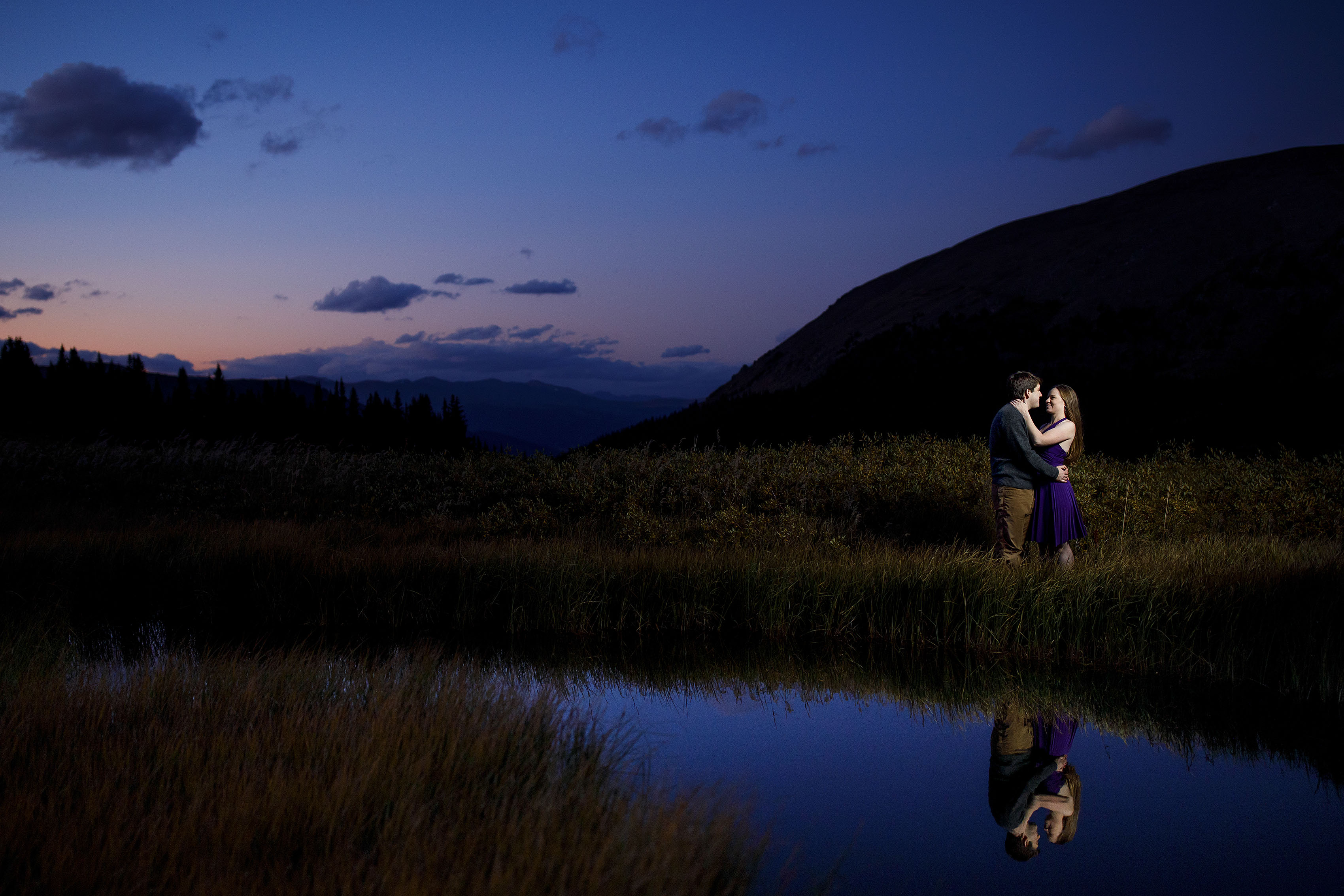 A couple is reflected in a high mountain pond as the sun sets at Guanella Pass during their engagement photos