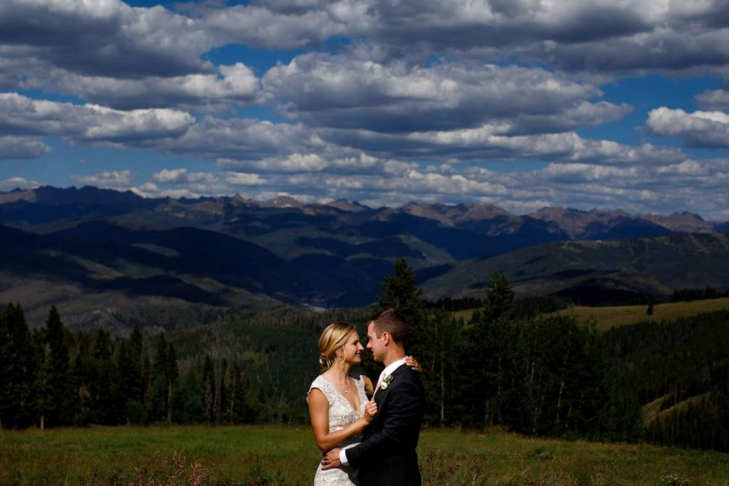 The bride and groom pose for a portrait near Solitude Station atop Beaver Creek mountain during their wedding