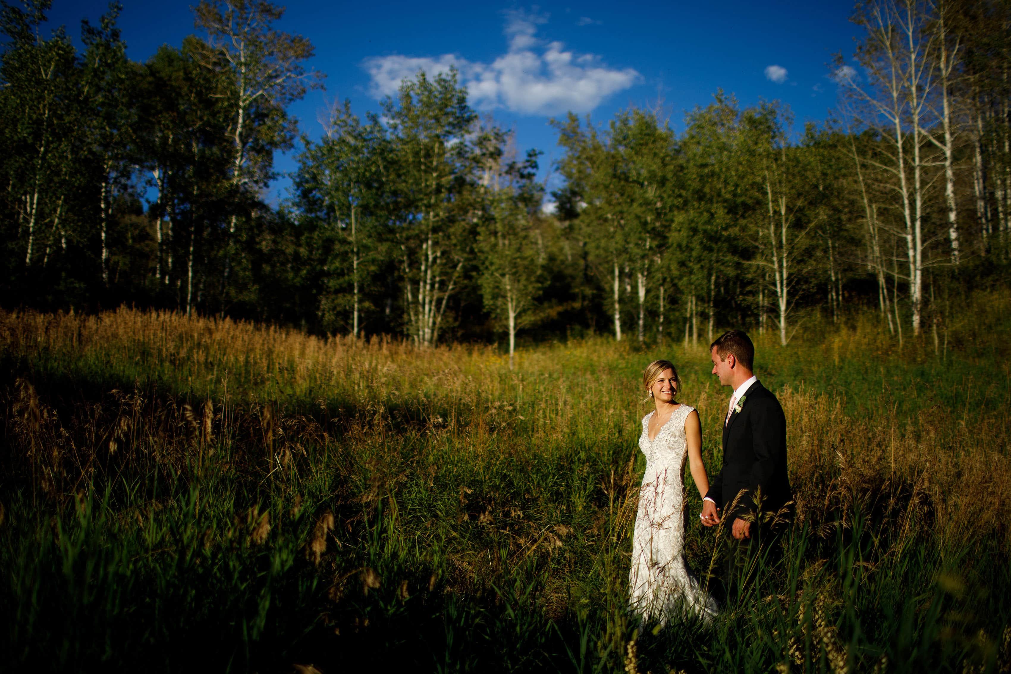 Melissa and Drew walk together in a field behind Saddleridge