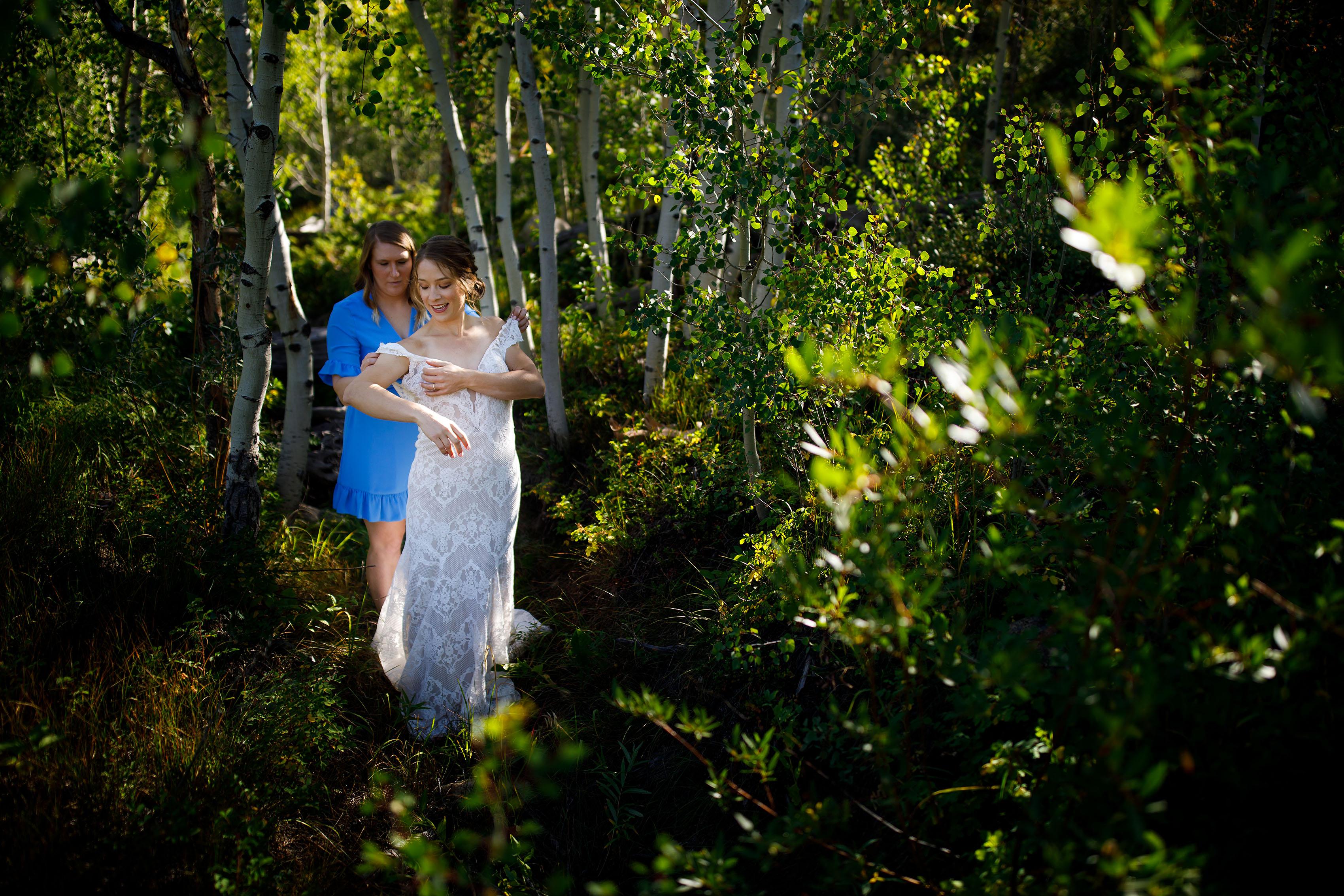 Carissa gets help putting her wedding dress on in an aspen grove