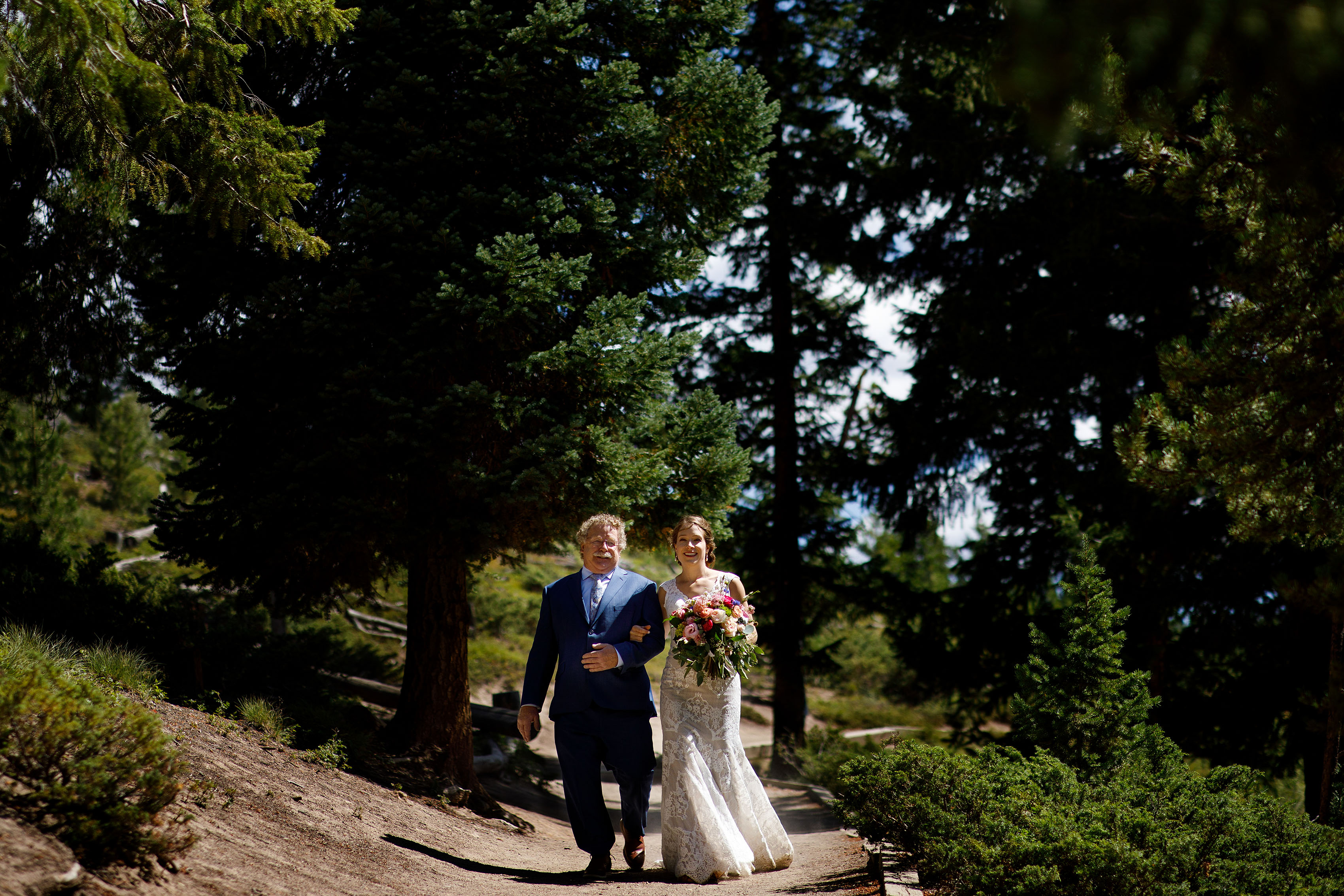 The bride walks down the path with her father at Sapphire Point