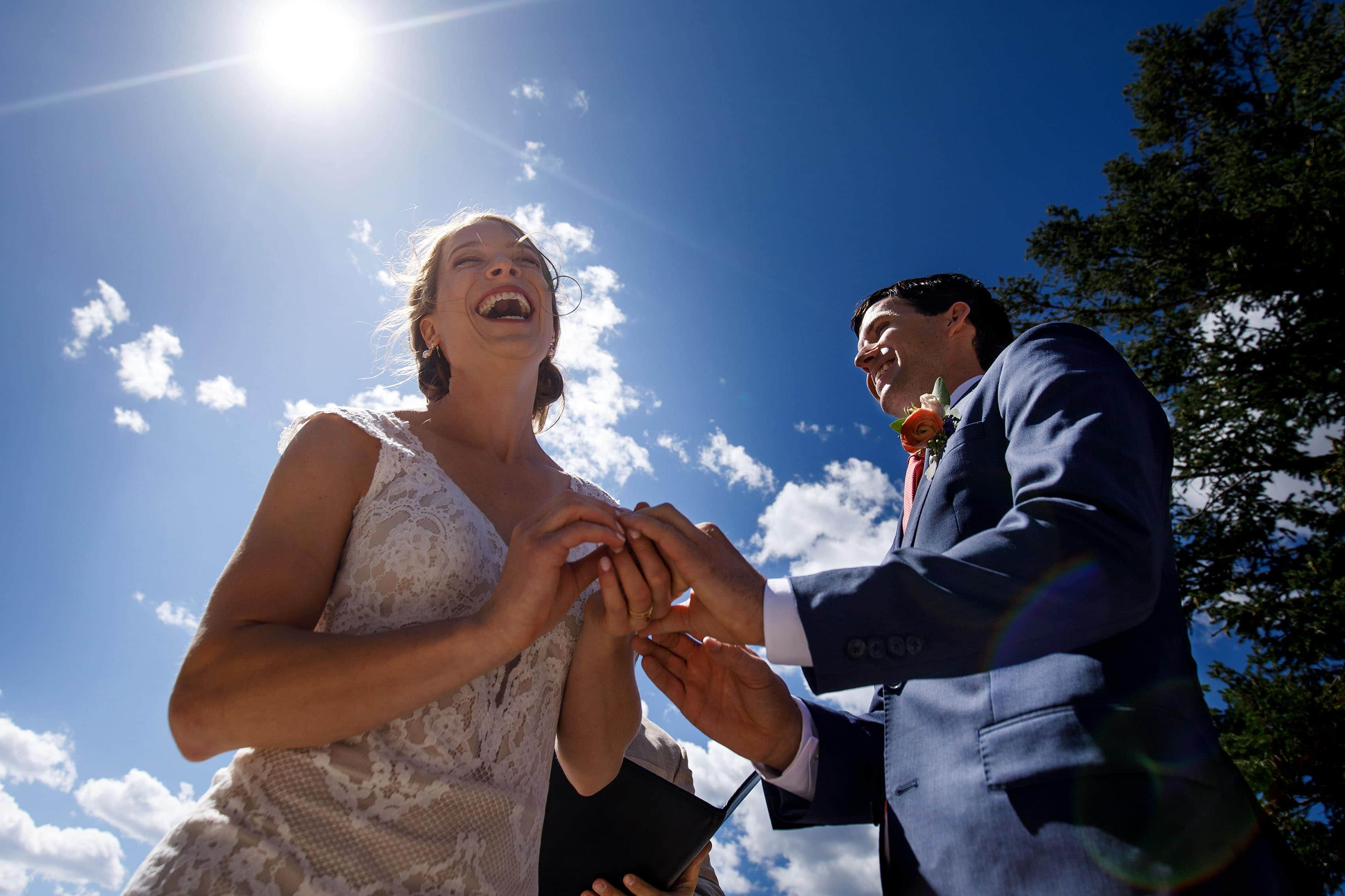 The bride laughs while putting on the groom's ring during their Sapphire Point wedding ceremony
