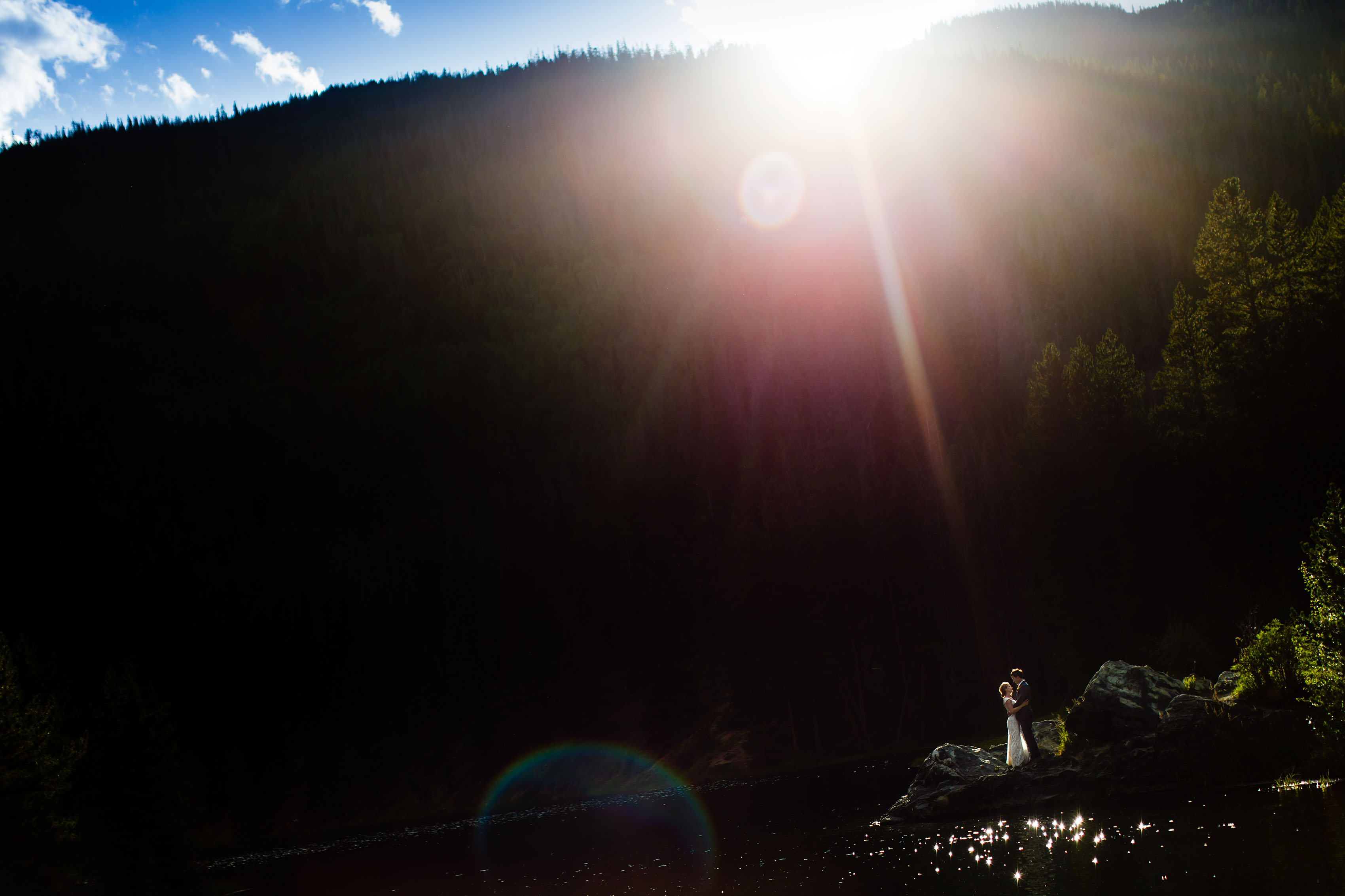 Sunlight flares over the ridge as Carissa and Kyle embrace on their wedding day at Officer's Gulch
