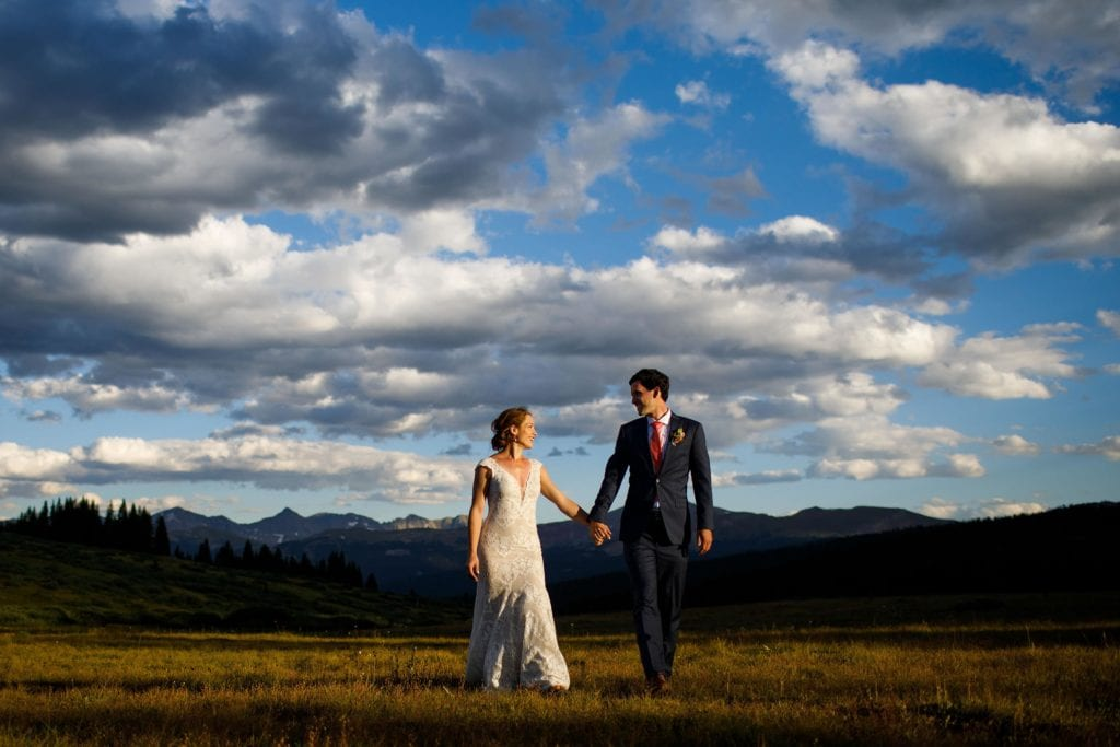 A bride and groom walk hand-in-hand as the sun sets atop Shrine Pass near Vail, Colorado