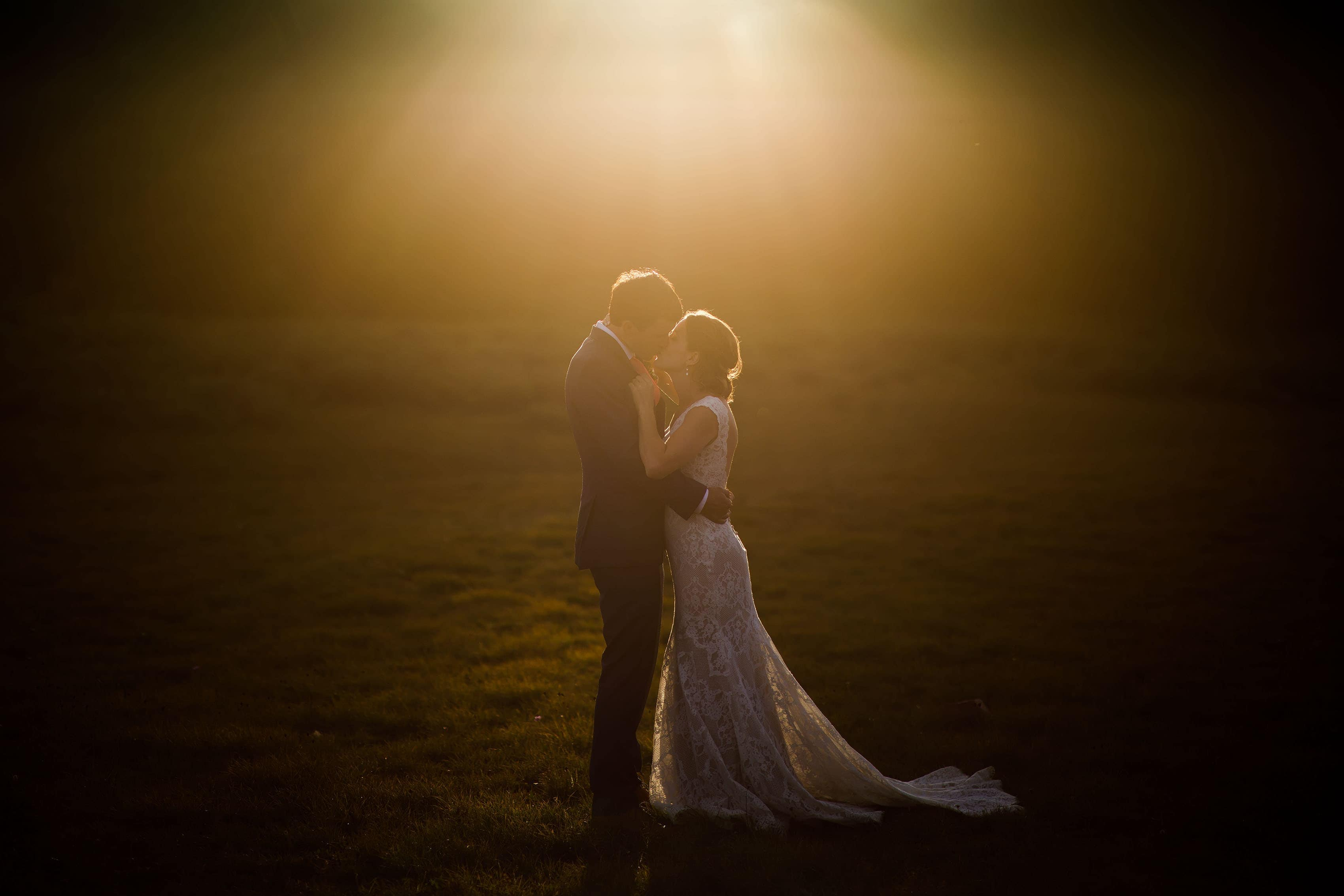 The sun sets as the bride and groom kiss at Shrine Pass