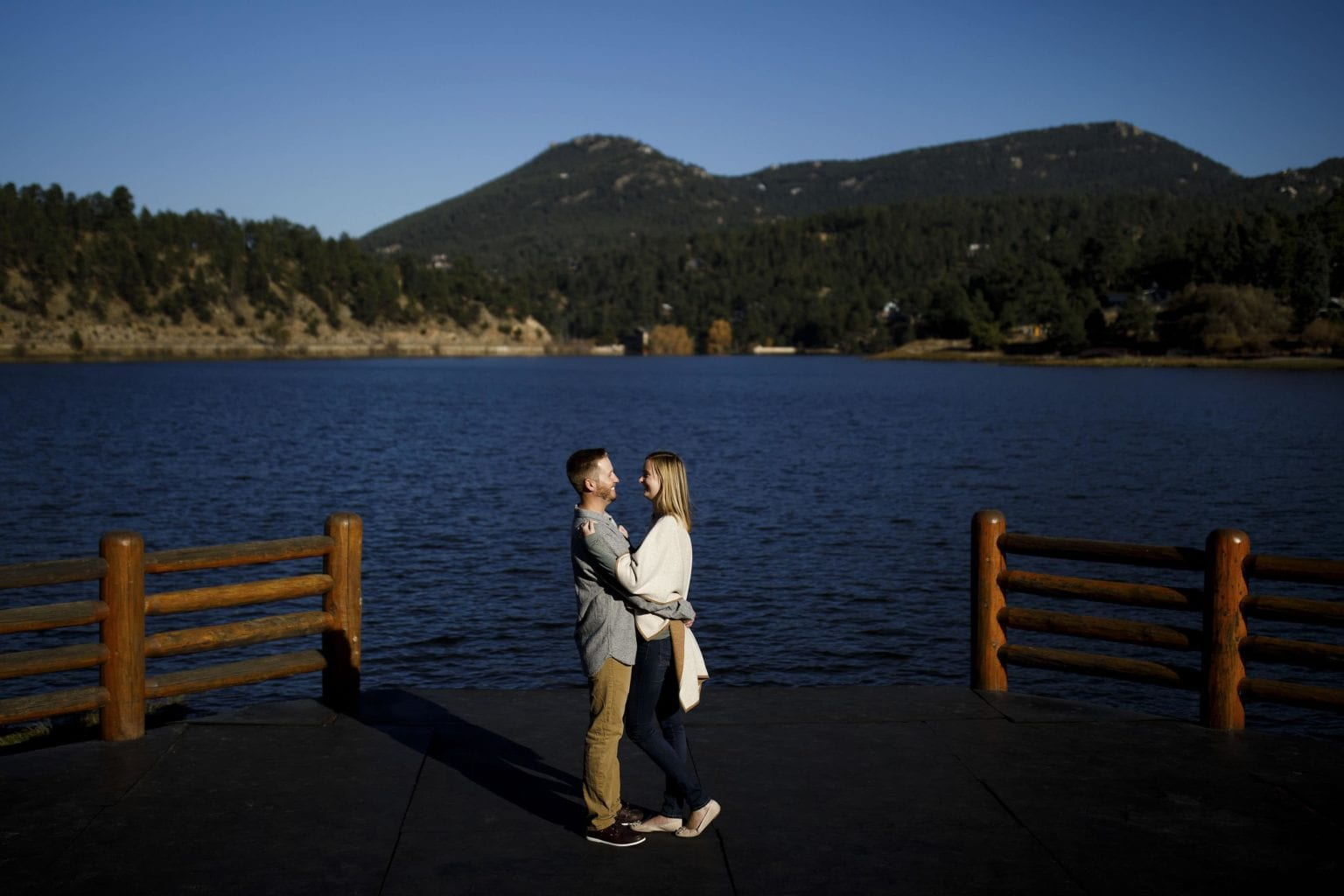 A couple poses at Evergreen Lake during their engagement photos in Evergreen, Colorado