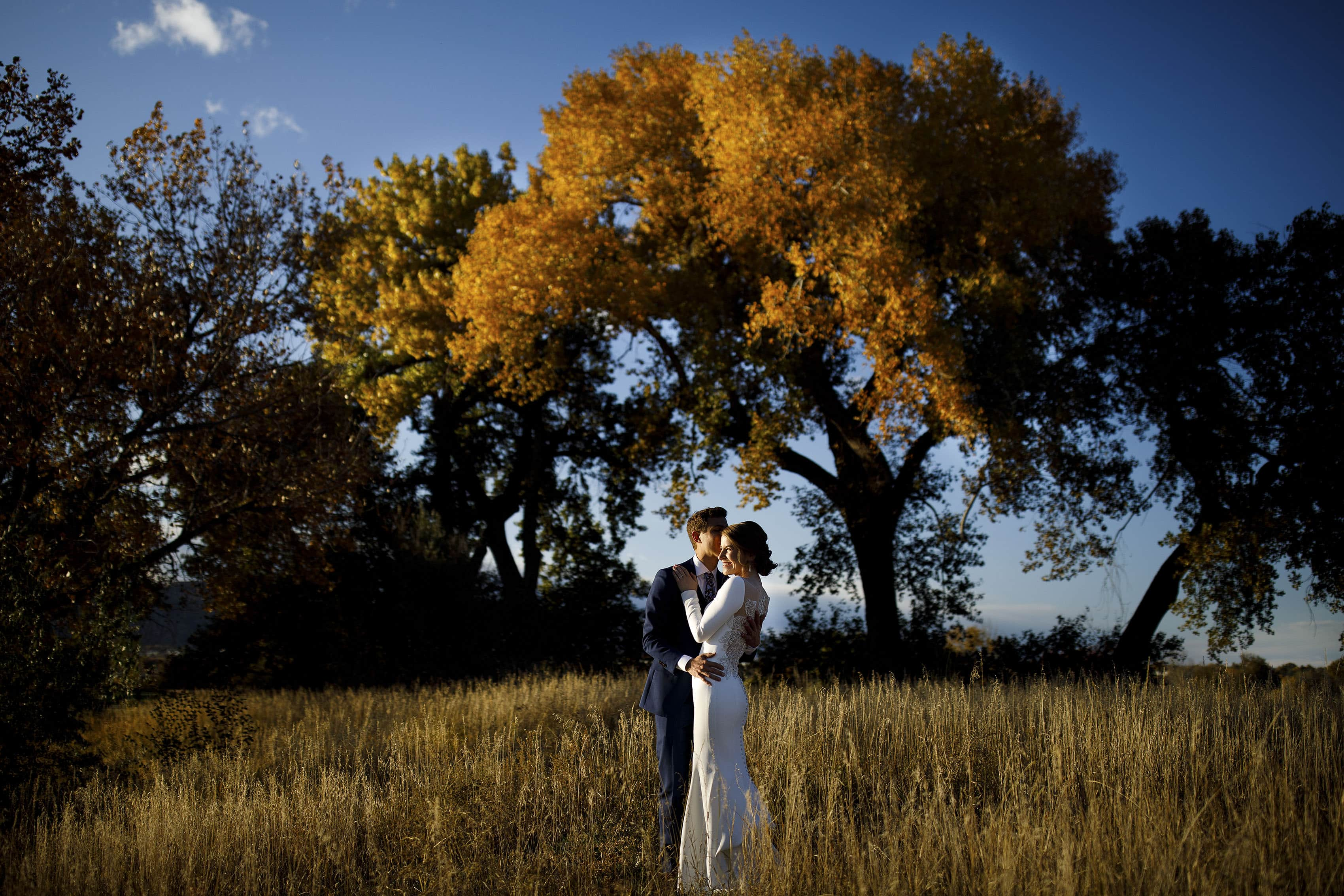 Mike kisses Jessica in a field near a colorful tree during their The Vista at Applewood Golf Course wedding day