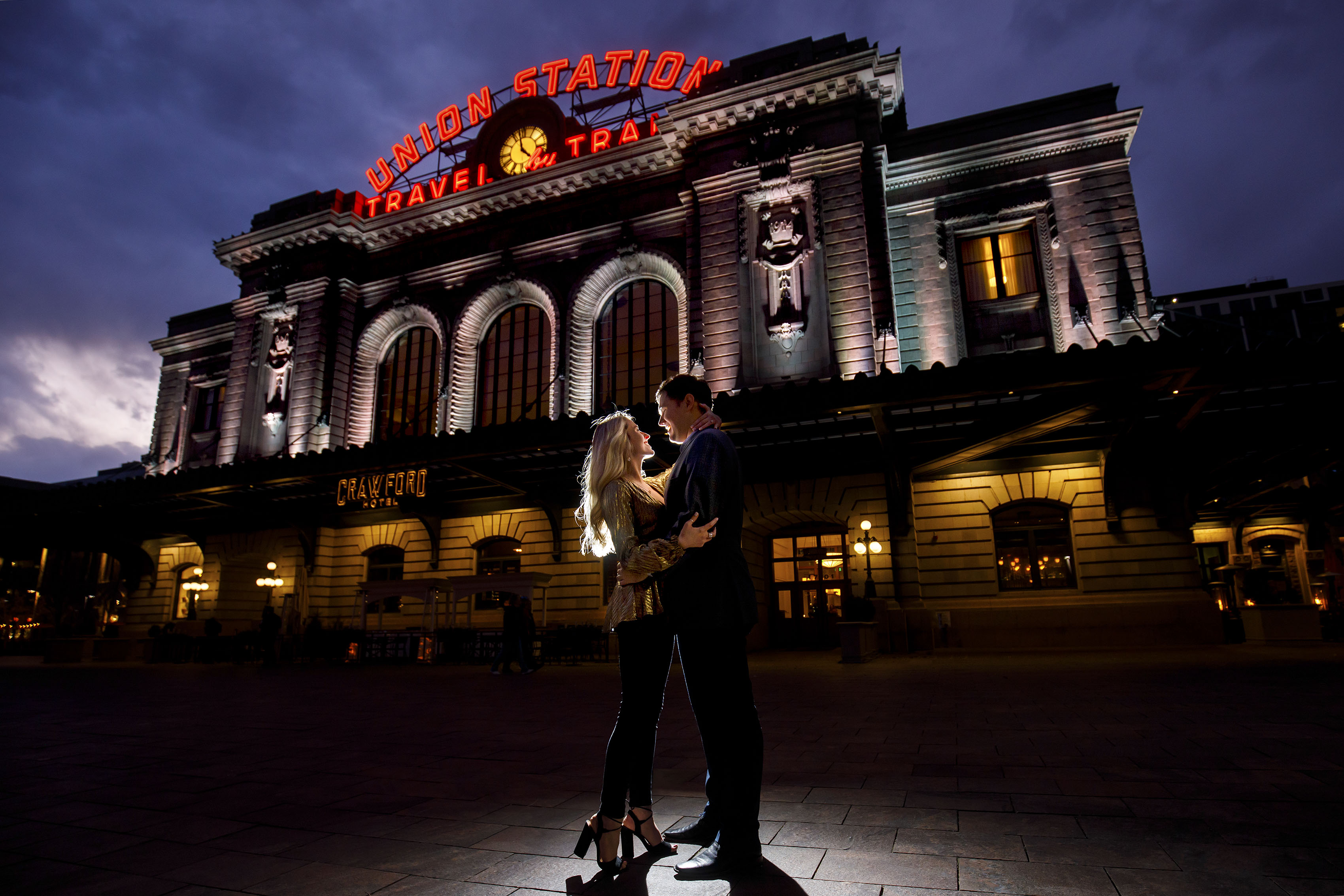 Sierra and Alex pose outside Denver's Union Station during twilight as they celebrate their recent engagement