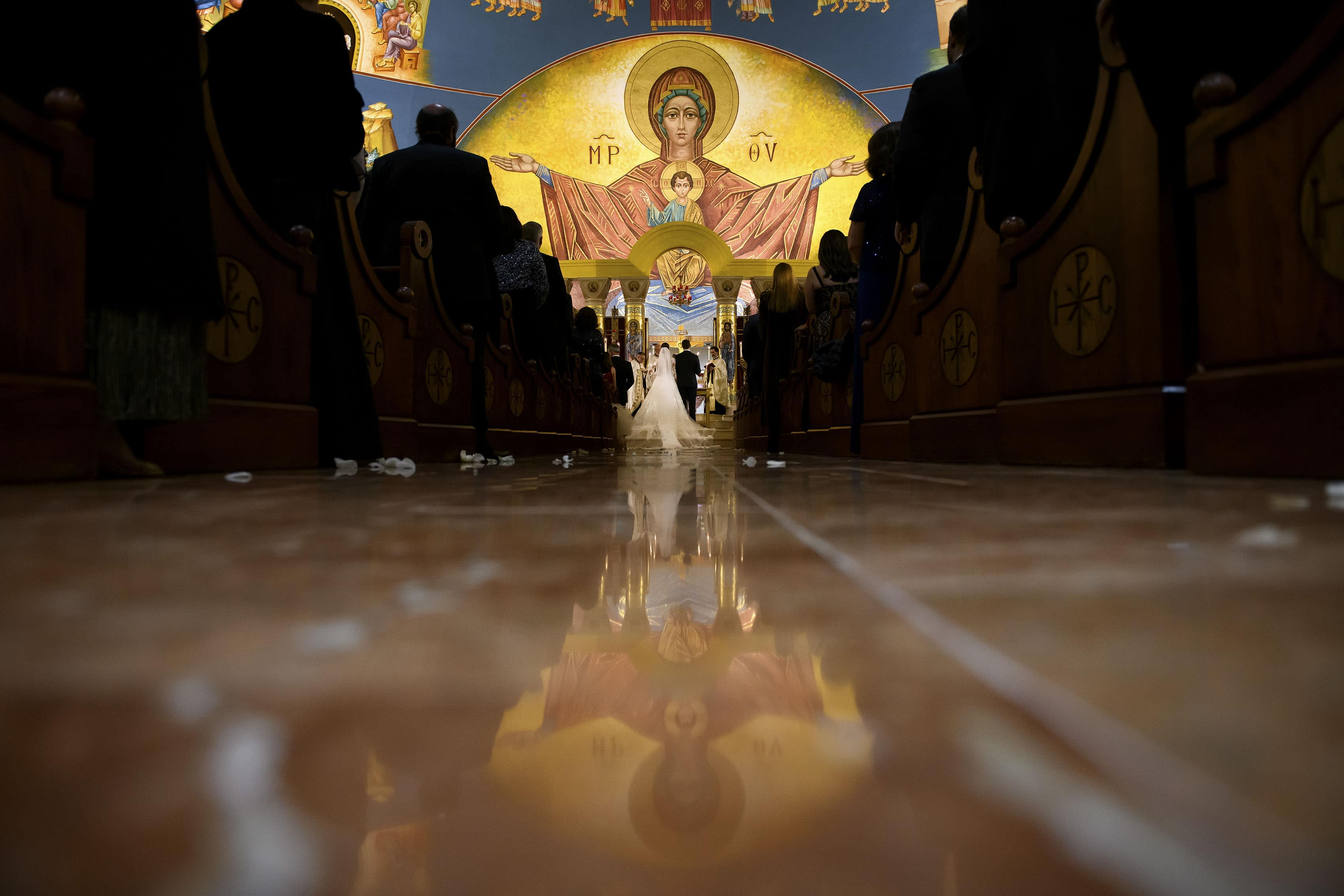 The bride and groom stand at the altar at the Assumption of the Theotokos Greek Orthodox Cathedral during their wedding ceremony