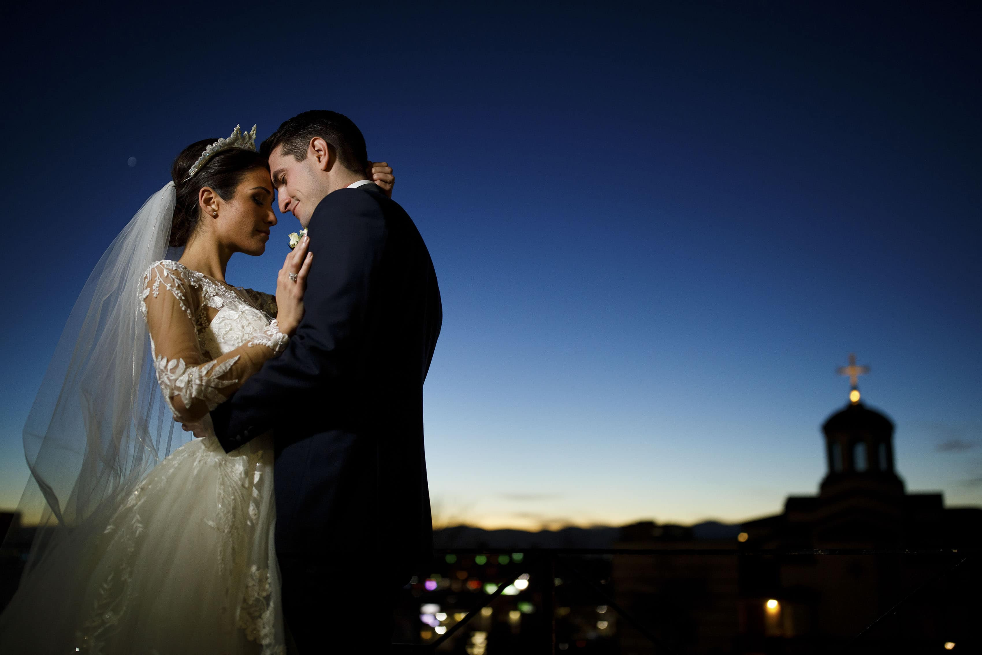 Newlyweds Alex and Ioanna share a moment outside the Assumption of the Theotokos Greek Orthodox Cathedral at twilight