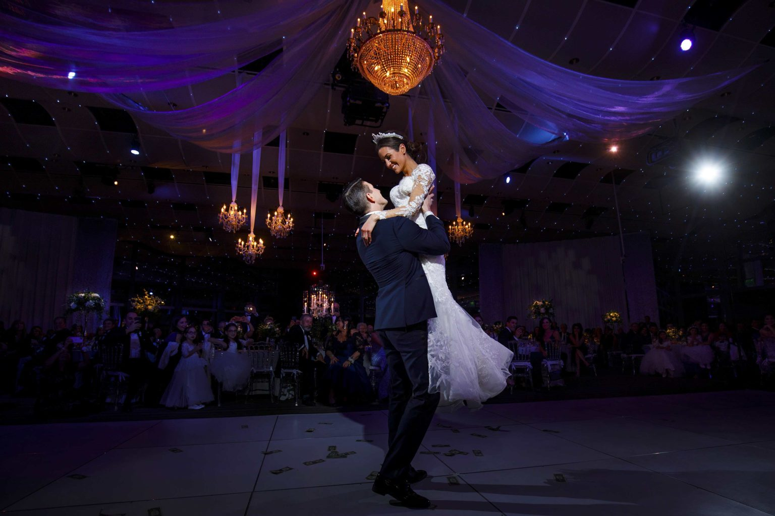 Alex lifts Ioanna on the dance loor during their colorful greek wedding in Denver at the Seawell Ballroom