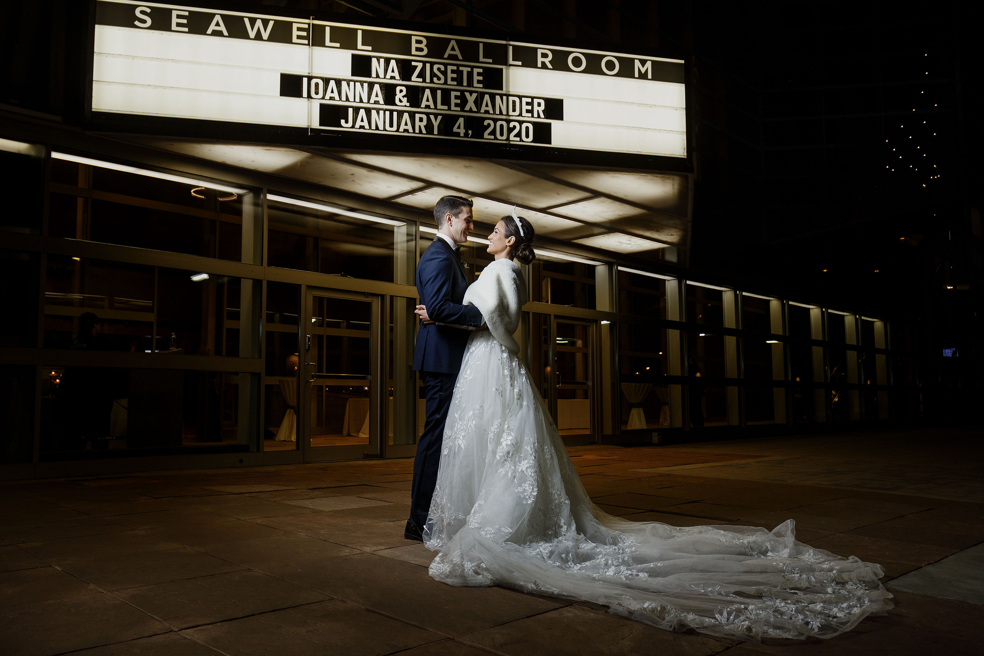 The bride and groom pose outside the marquee at Seawell Ballroom at the Denver Center for the Performing Arts