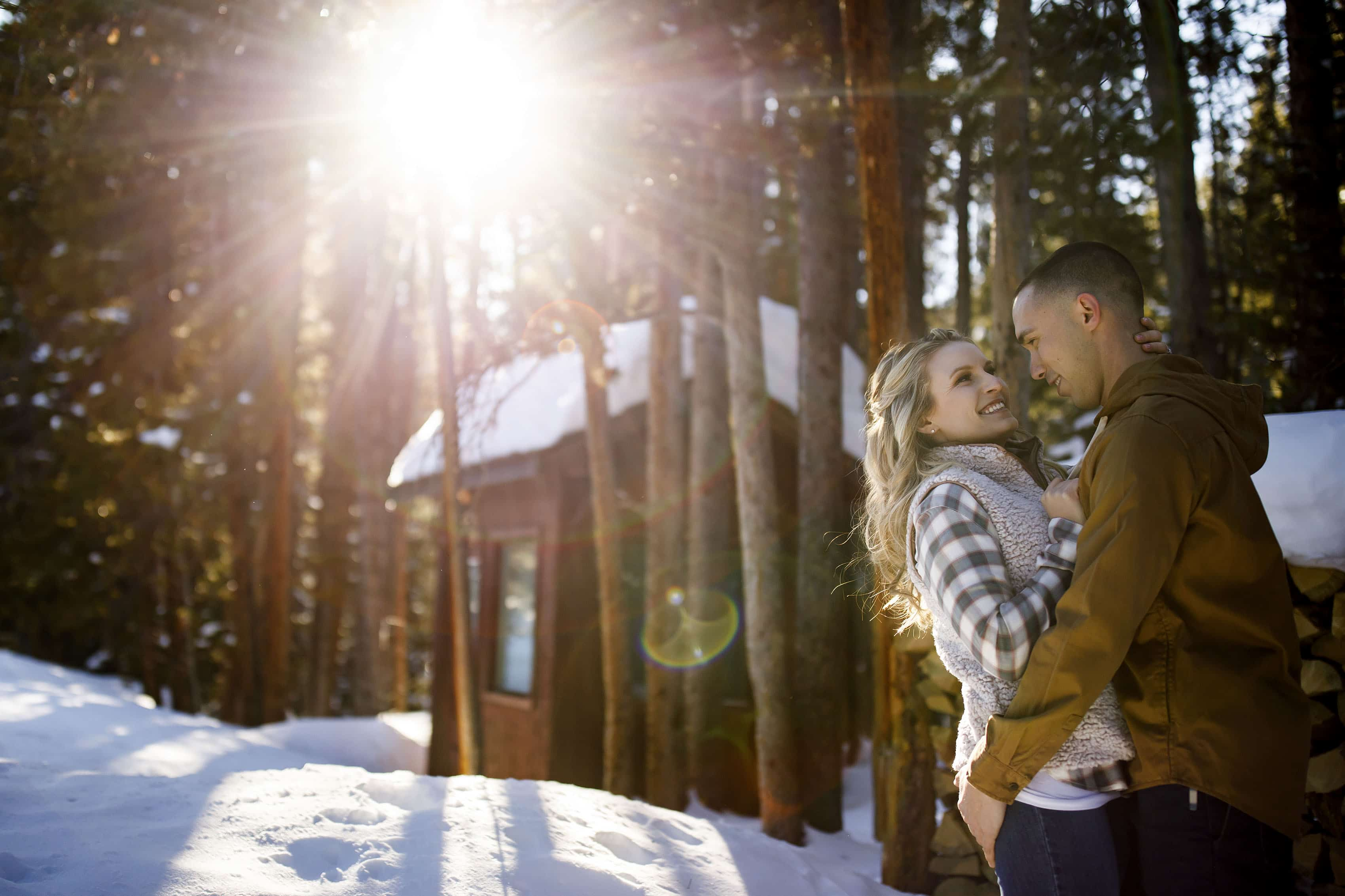 Shane and Cassidy embrace as the sunlight filters through the trees at Sawmill reservoir in Breckenridge during their winter engagement session
