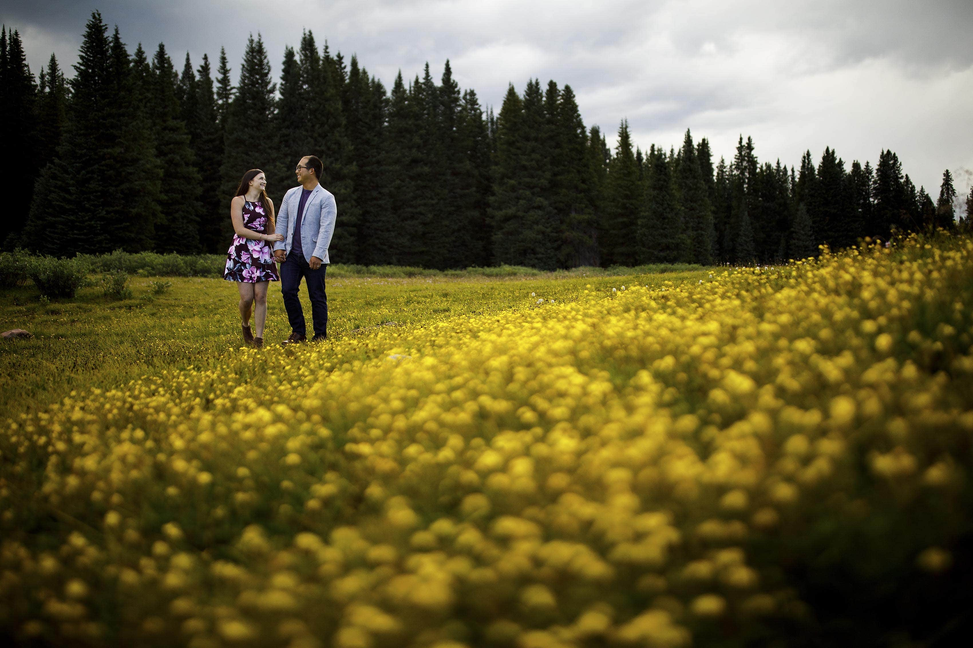 Courtney and Mike walk through a field of yellow wild flowers during their Shrine Pass engagement session in Colorado